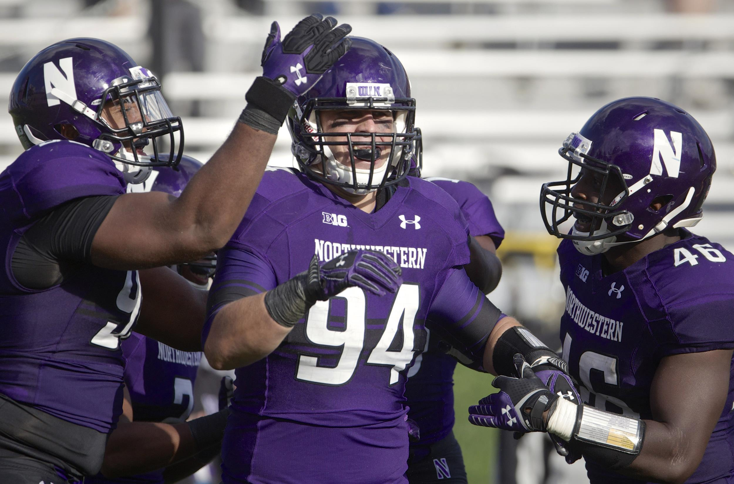 Image: Dean Lowry #94 of the Northwestern Wildcats is congratulated by teammates Chance Carter #99 and Damien Proby #46 after scoring a touchdown