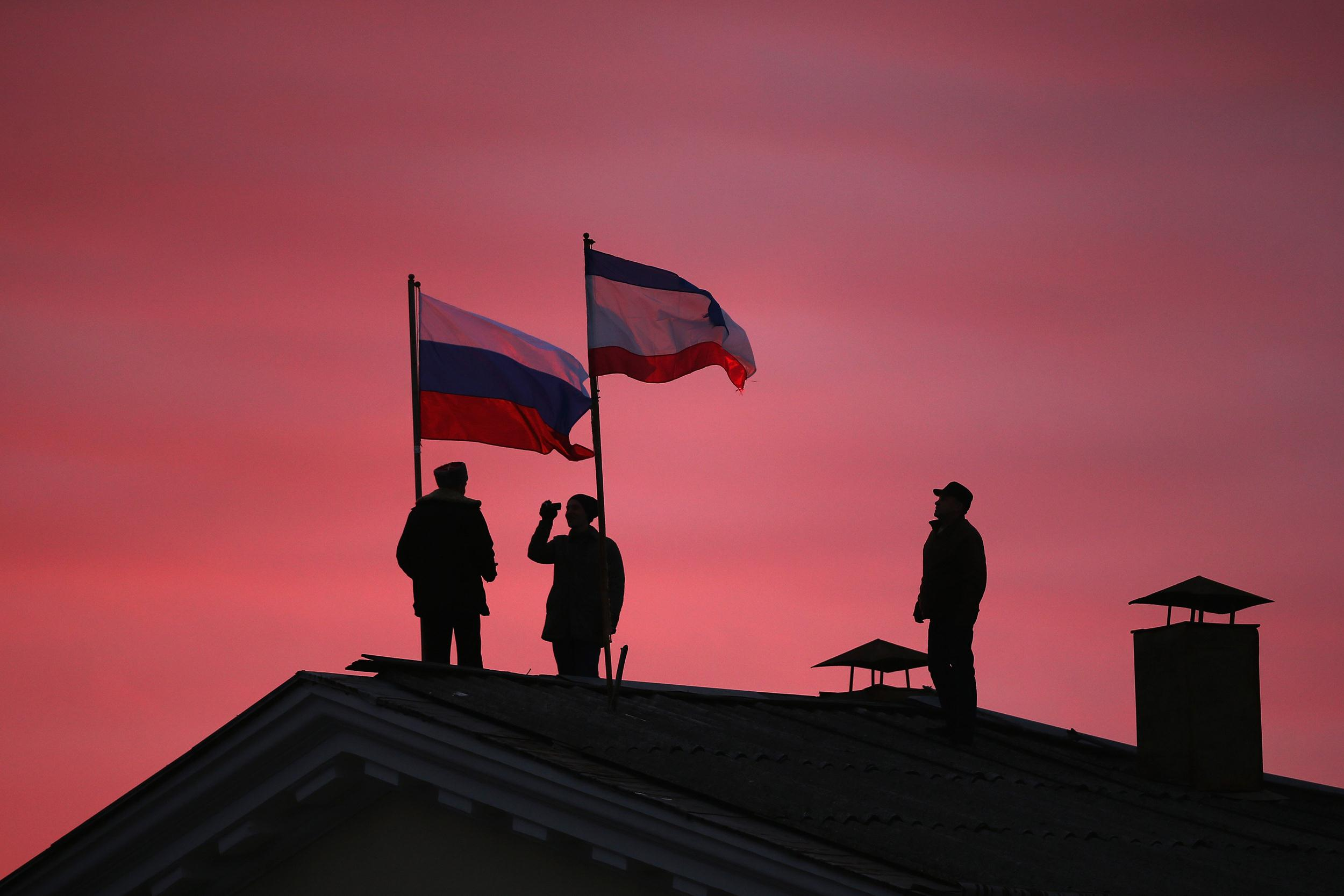 Image: Cossack men install a Russian flag and a Crimean flag