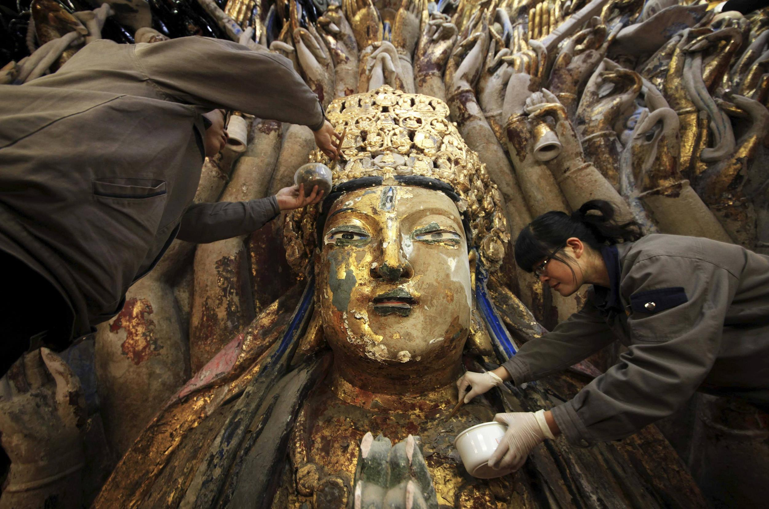 Image: Workers peel off loose gold foil as part of a restoration project for a Thousand-Hand Guanyin Buddhist statue in Chongqing