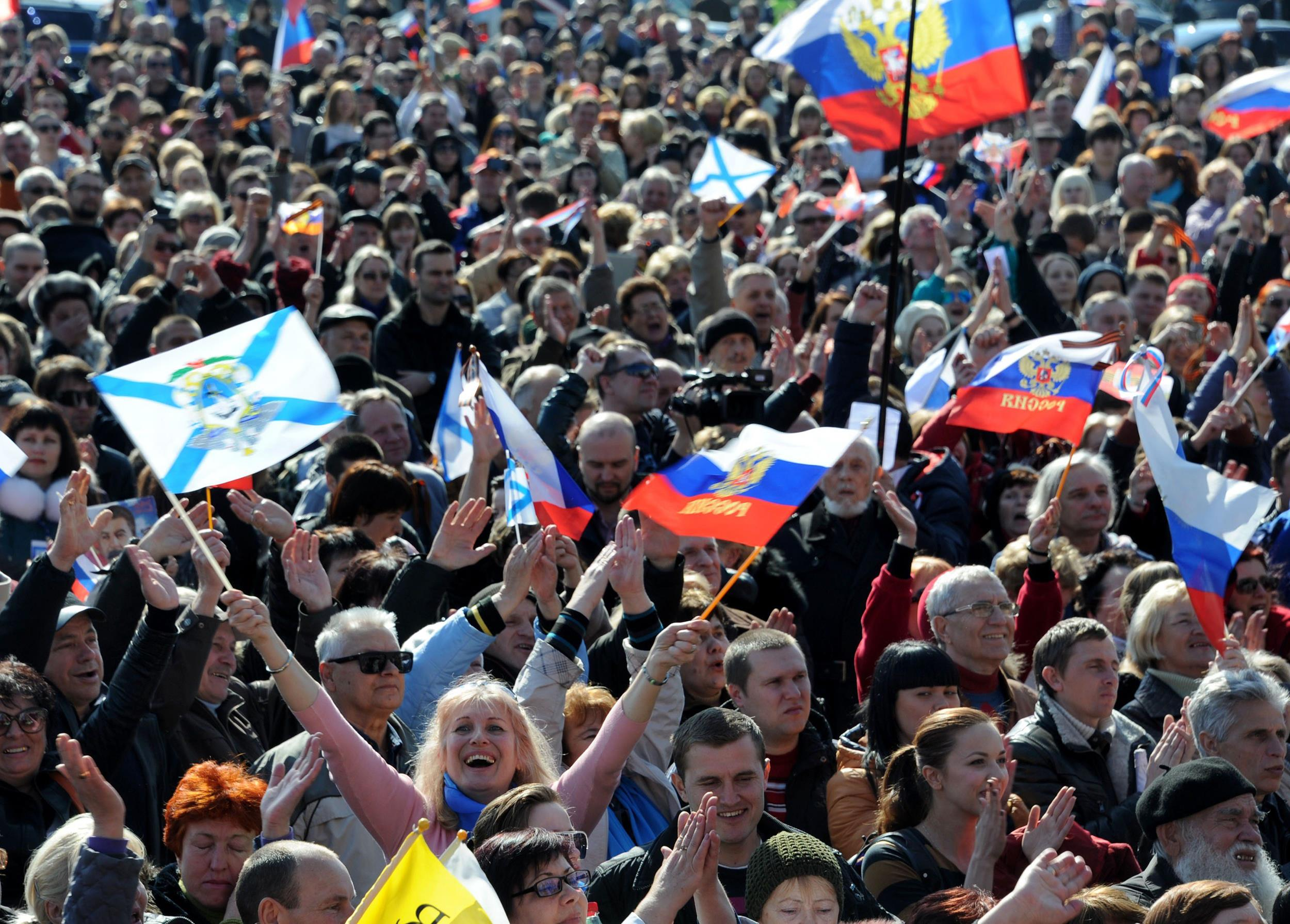 Image: People listen to a speech by  Russian President Vladimir Putin as it is broadcast on a giant screen in Sevastopol, Crimea, on Tuesday.