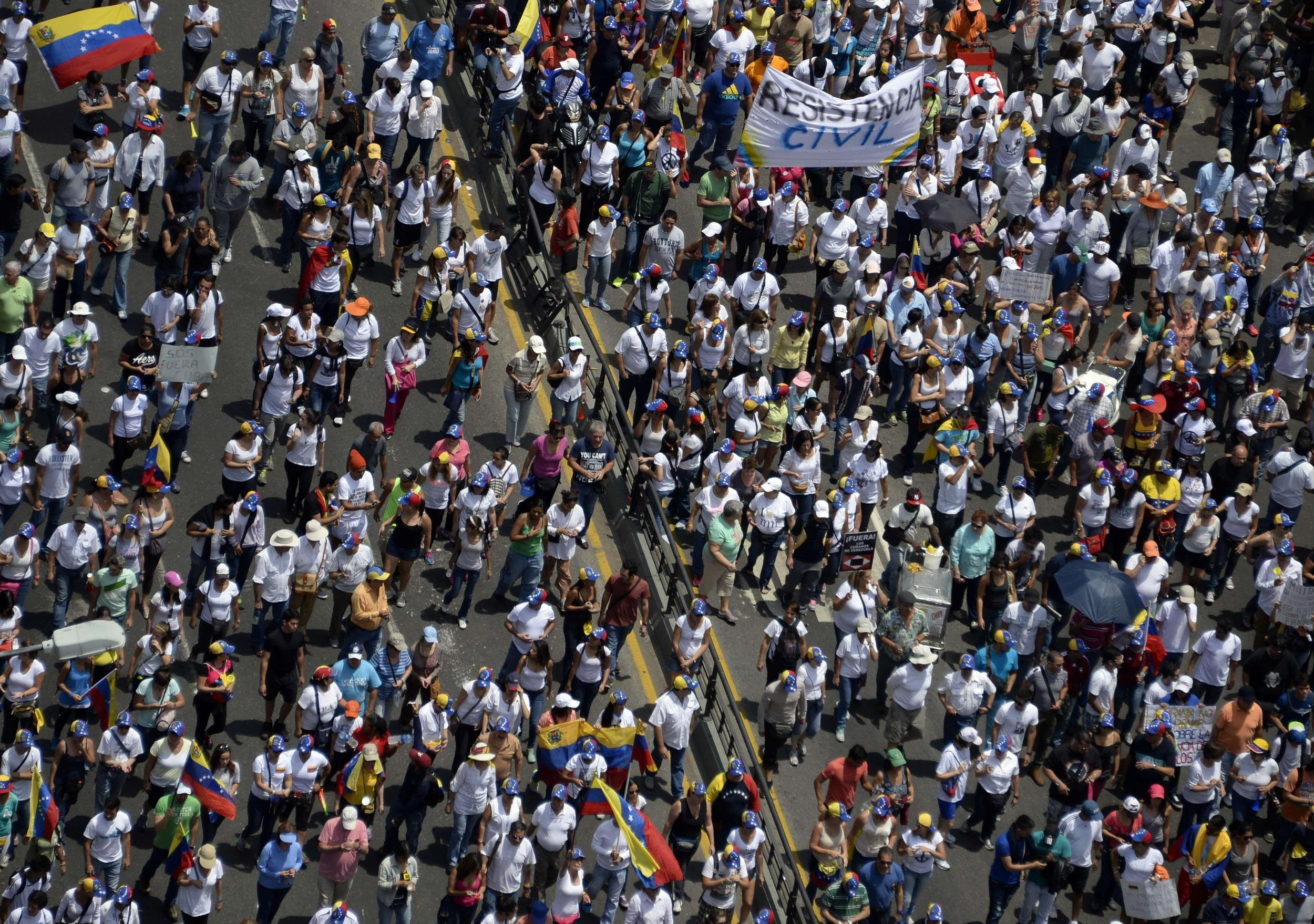 Opposition activists march toward the Cuban embassy to protest against Cuban interference in Venezuela's internal affairs