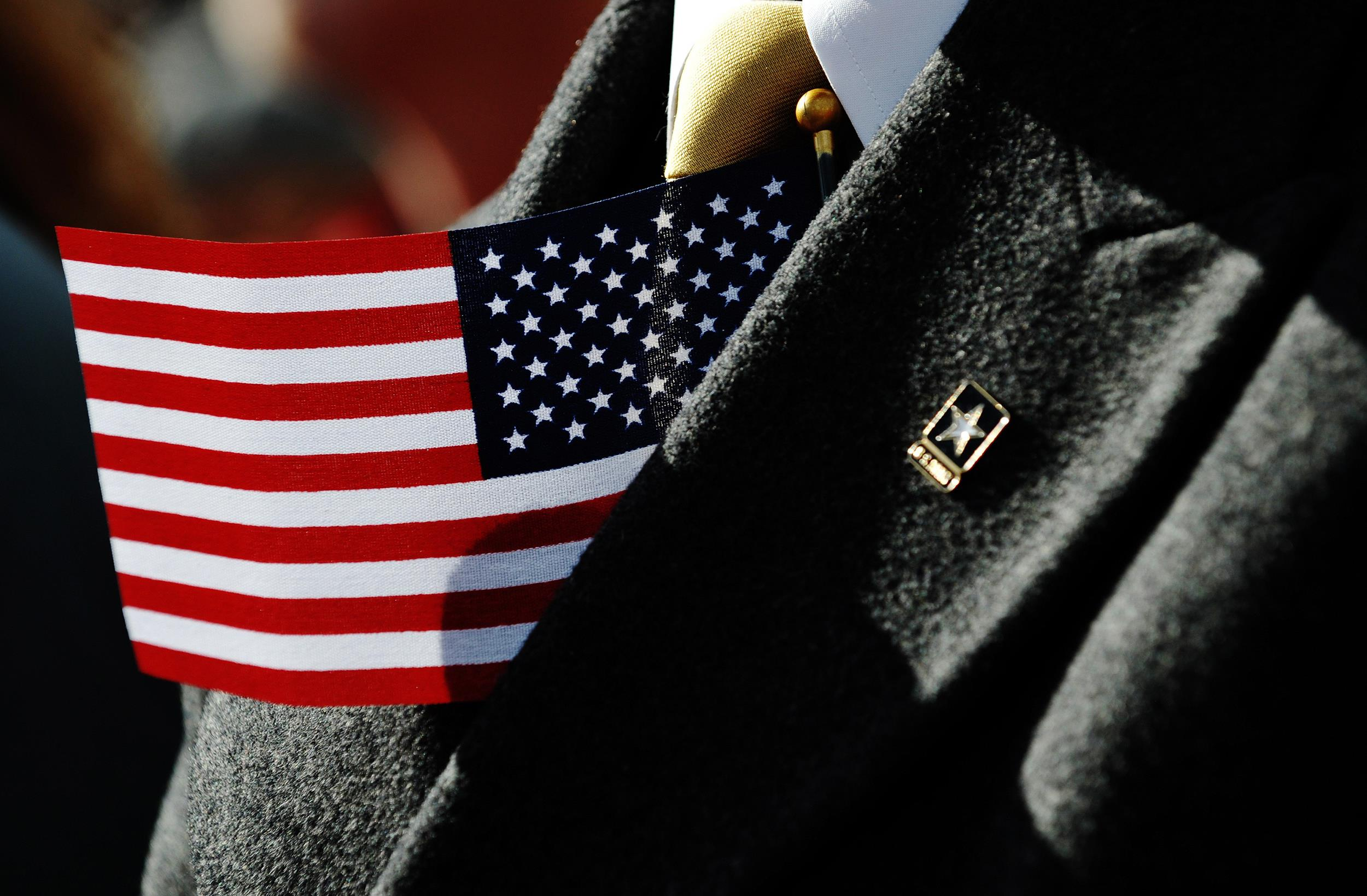 Image: A U.S flag is tucked into the jacket of a man