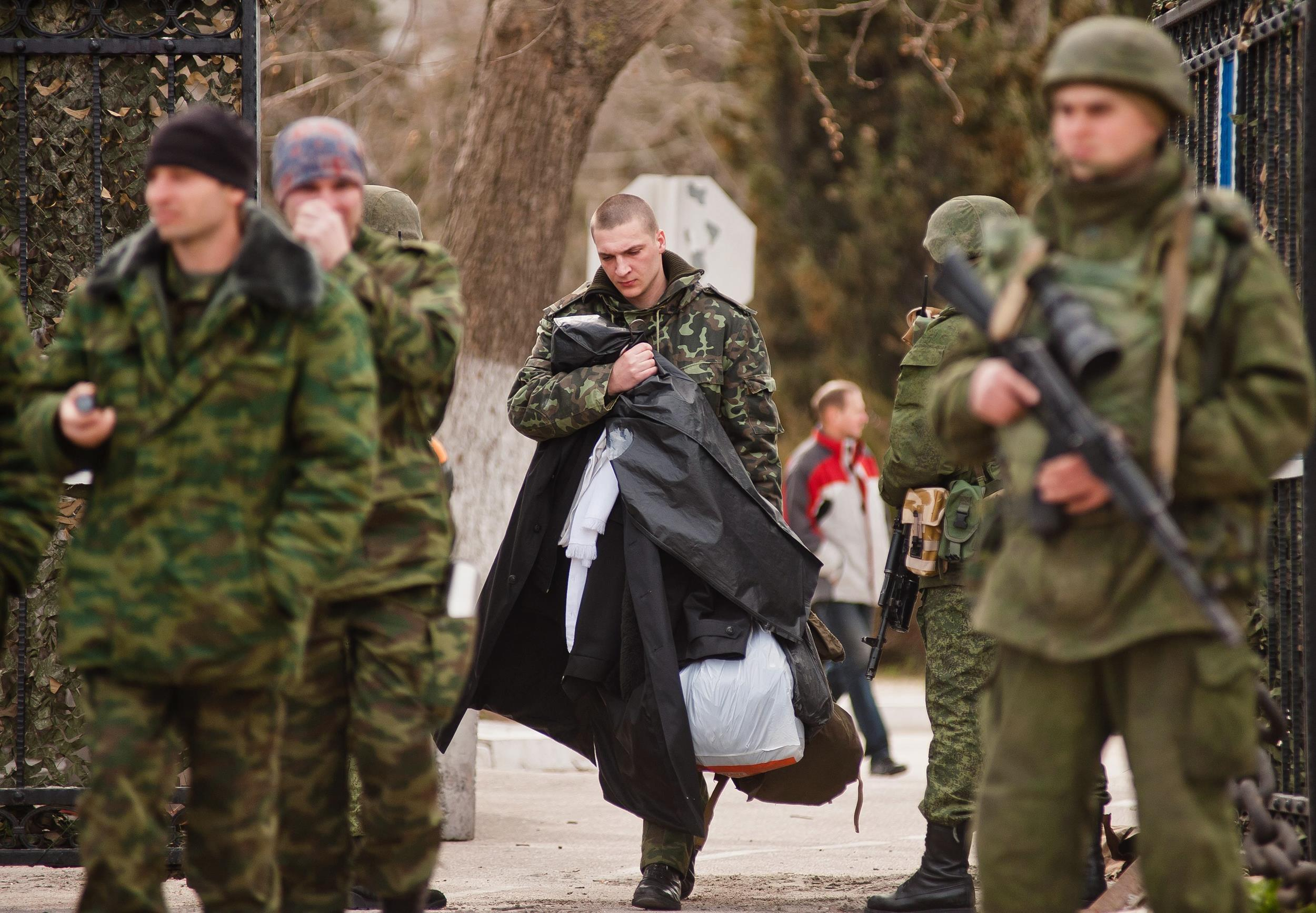 Image: A Ukrainian serviceman leaves the territory of a Ukrainian military unit as armed men in military uniform control it in Sevastopol