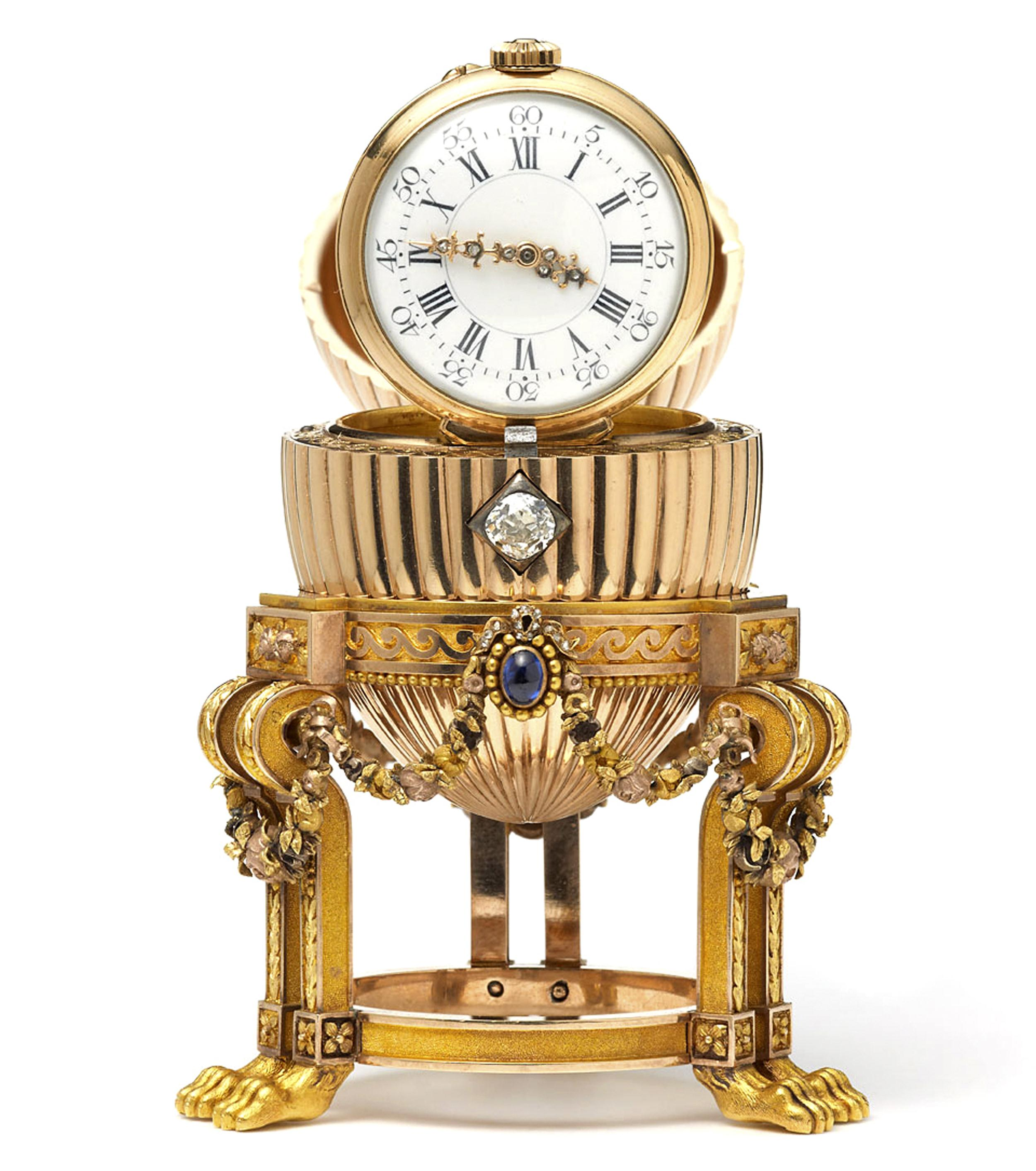 Image: A rare Imperial Faberge Egg with the top open to reveal a clock