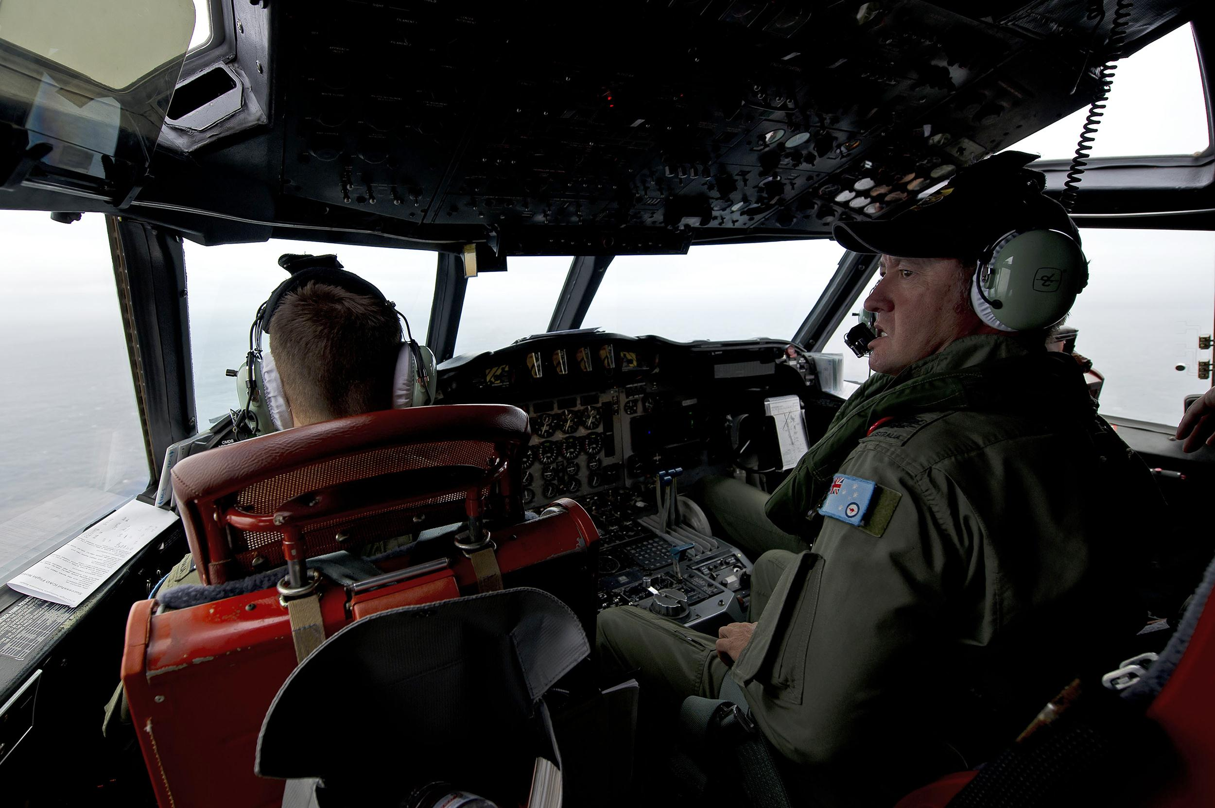 Image: A Royal Australian Air Force flight engineer aboard a AP-3C Orion aircraft keeps watch for any debris