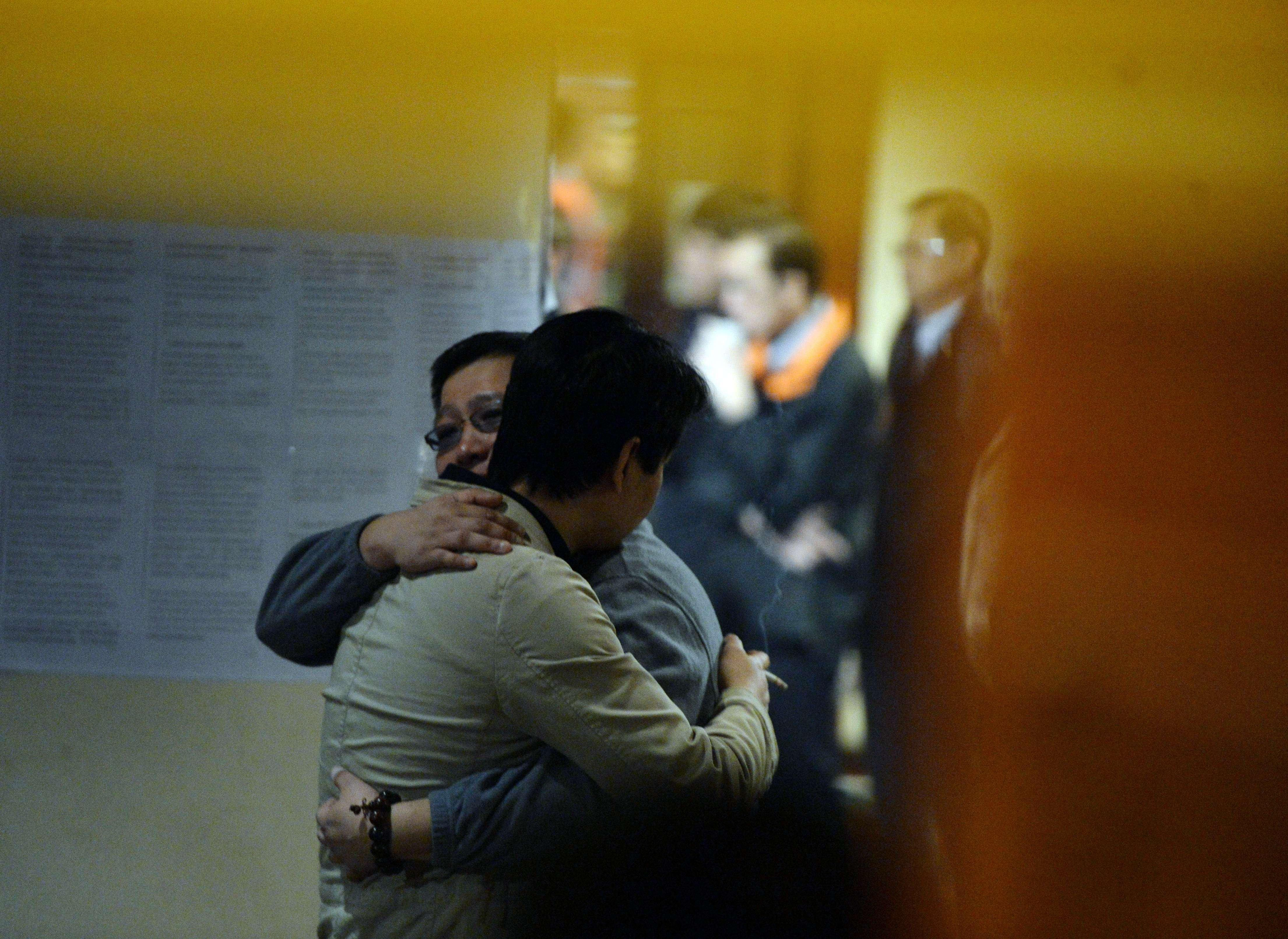 Image: Chinese relatives of passengers from the missing Malaysia Airlines Flight MH370 console each other