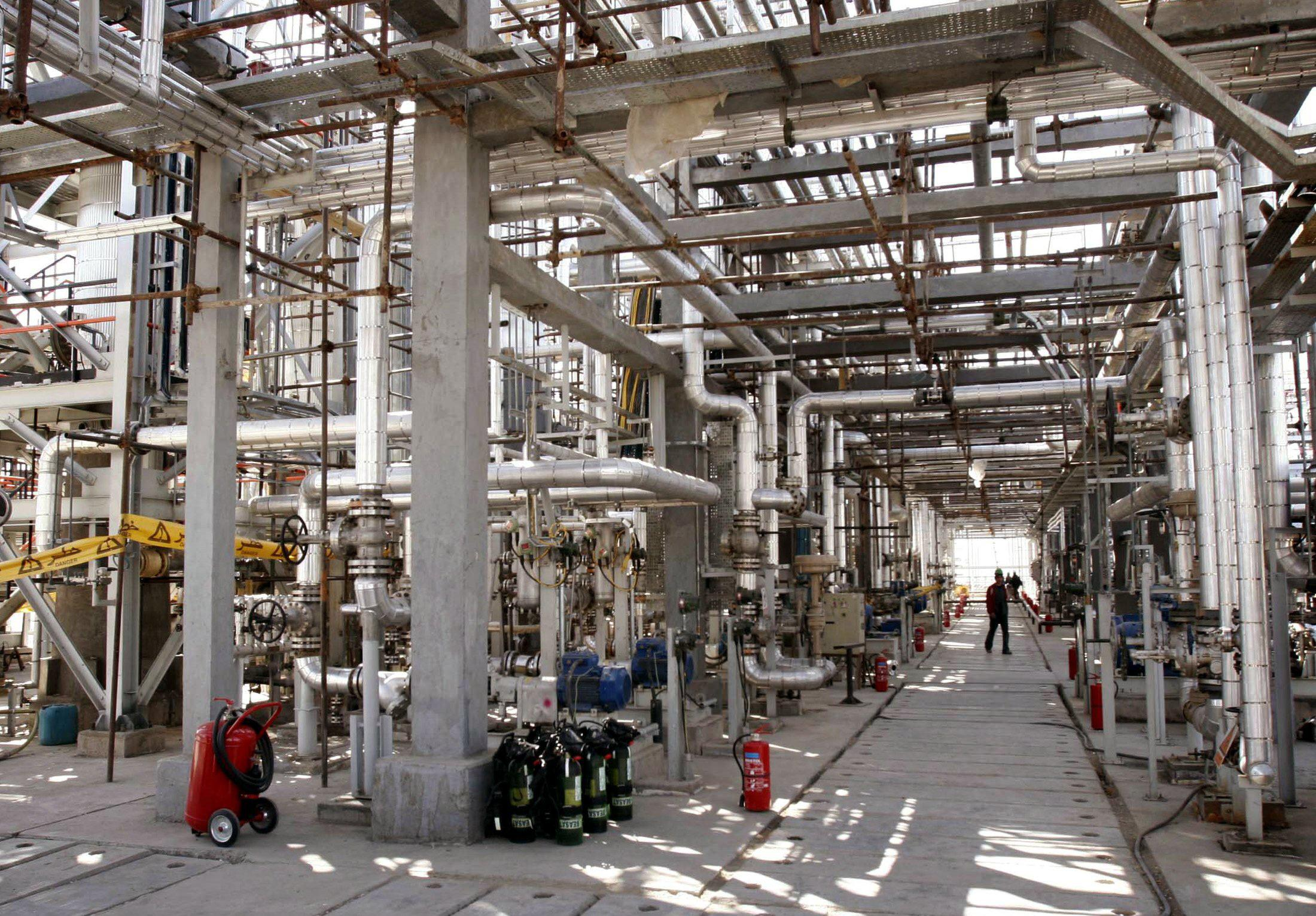 Image: A worker walks through a maze of pipes at the Arak