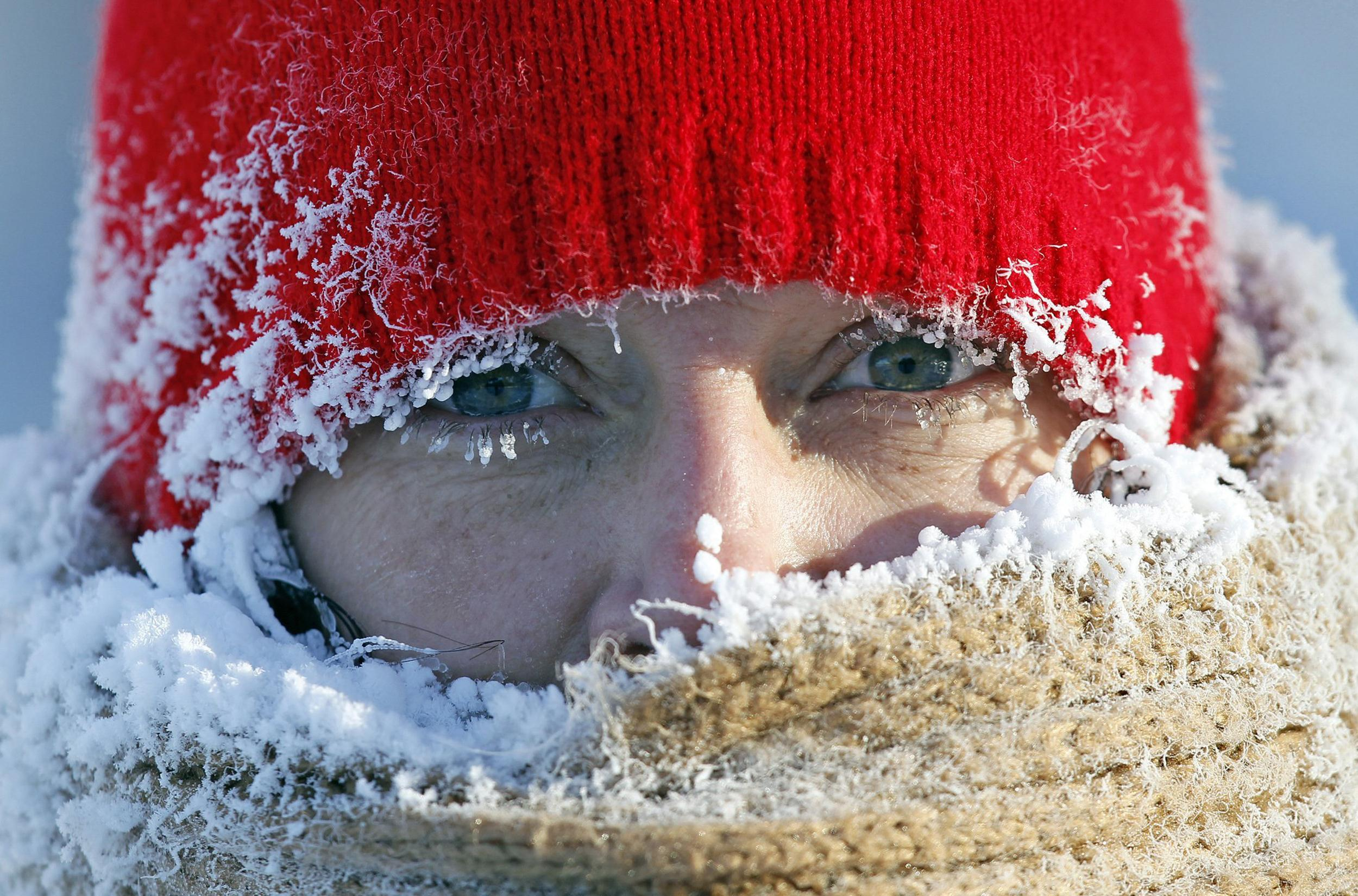 Image: Frost forms around the face of a woman walking outside in Minneapolis