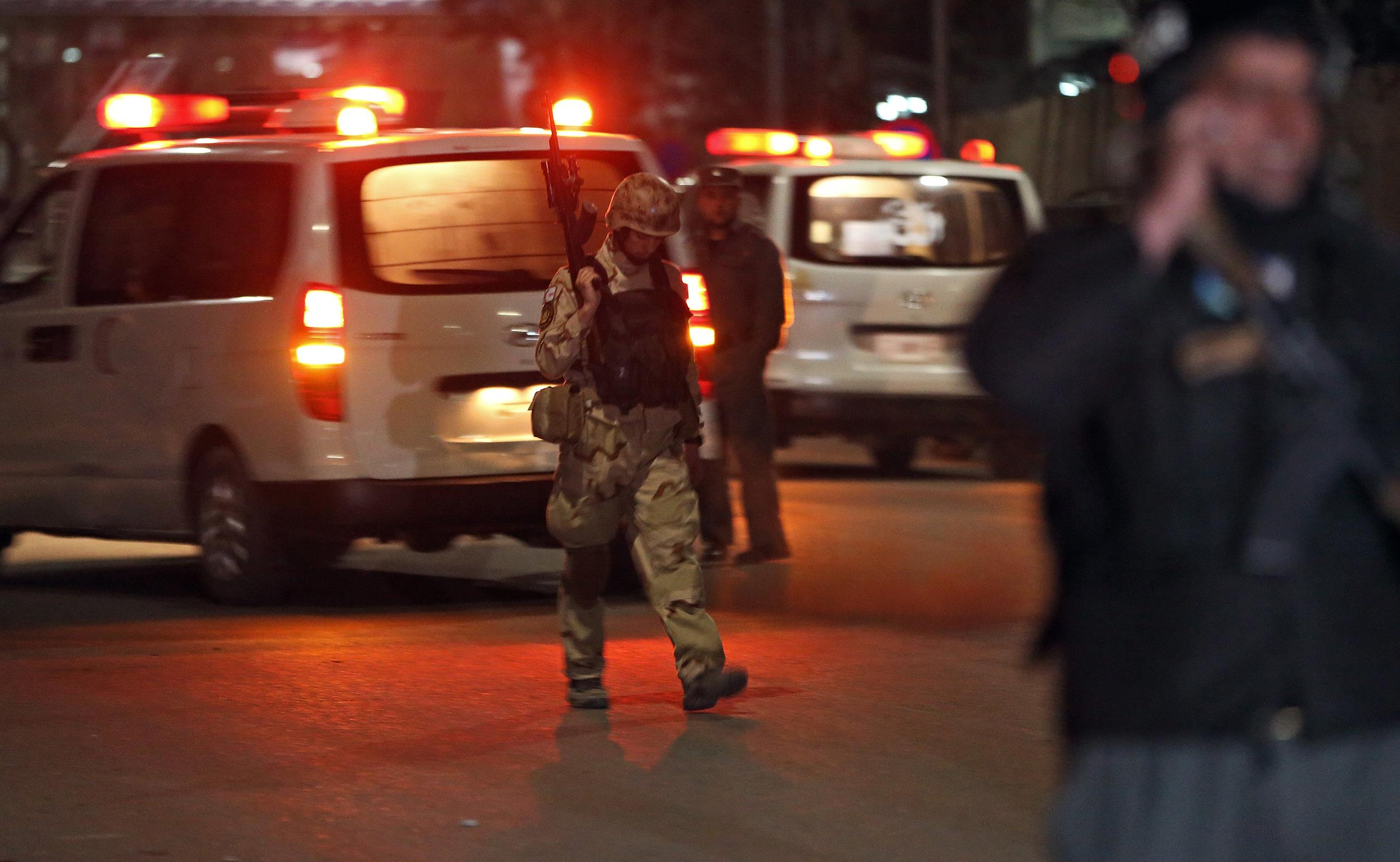 Image: An Afghan policeman walks at the site of a gun battle in Serena Hotel in Kabul