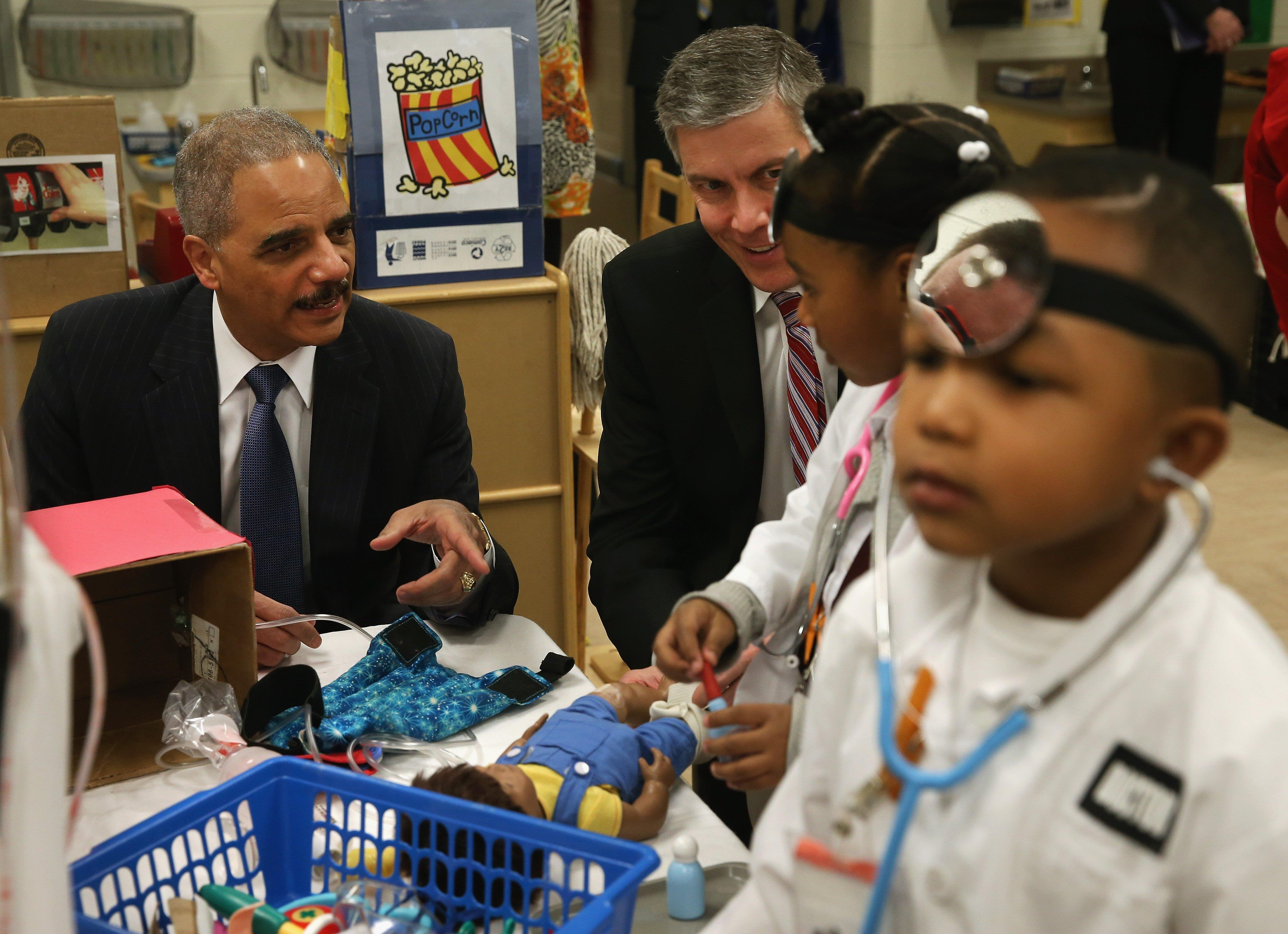 Image: Eric Holder And Arne Duncan Visit Washington DC Elementary School