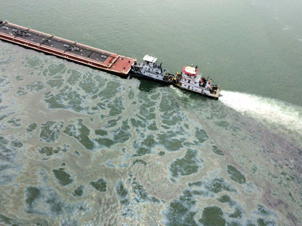 Image: A barge loaded with marine fuel oil sits partially submerged in the Houston Ship Channel, March 22, 2014.