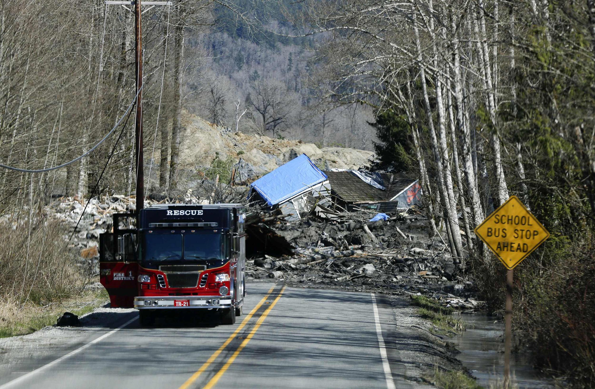 Image: A emergency vehicle is parked as a landslide and debris block Highway 530 near Oso, Wash.