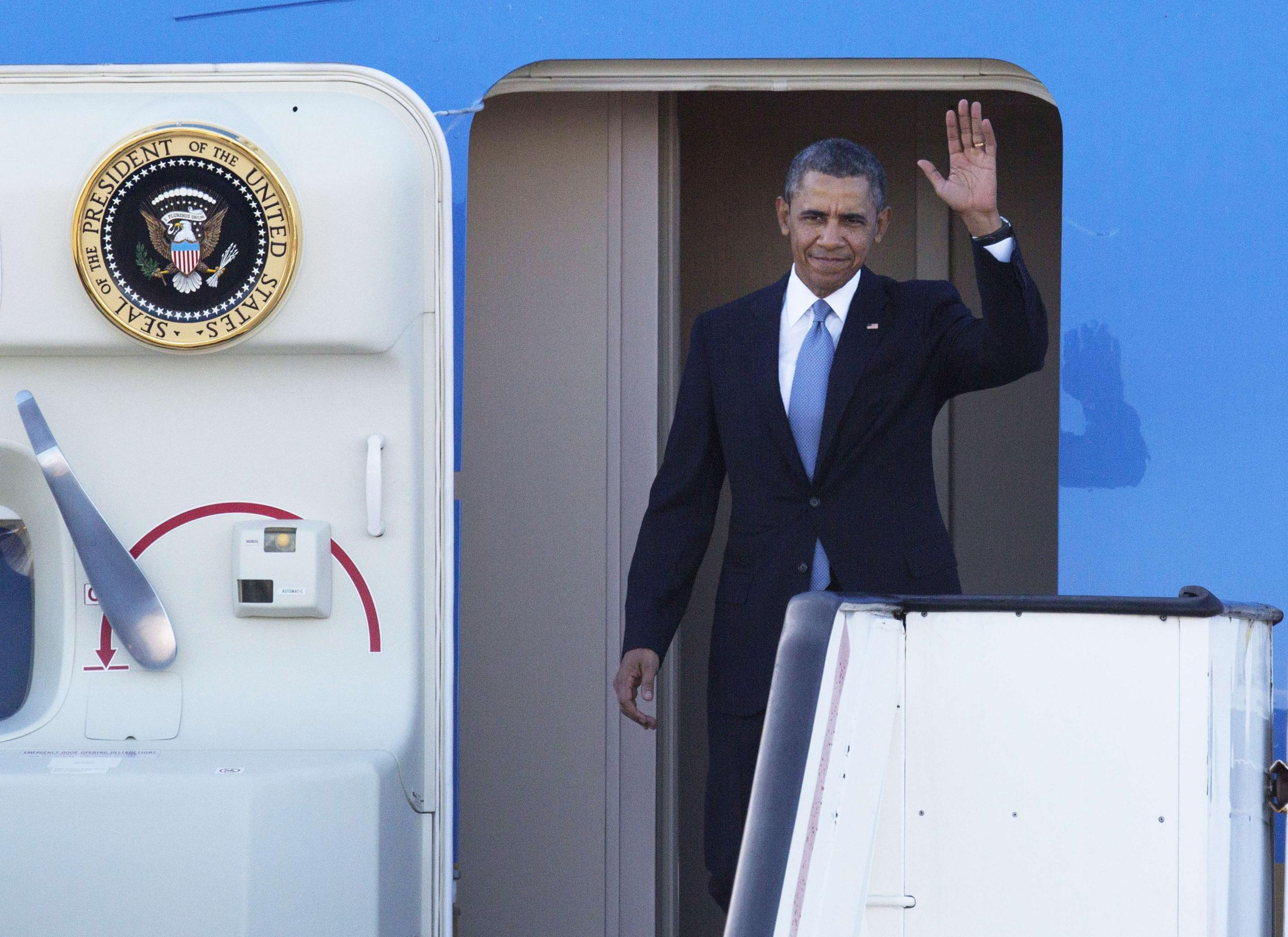 Image: President Barack Obama waves as he disembarks from Air Force One upon his arrival at Schiphol Amsterdam Airport