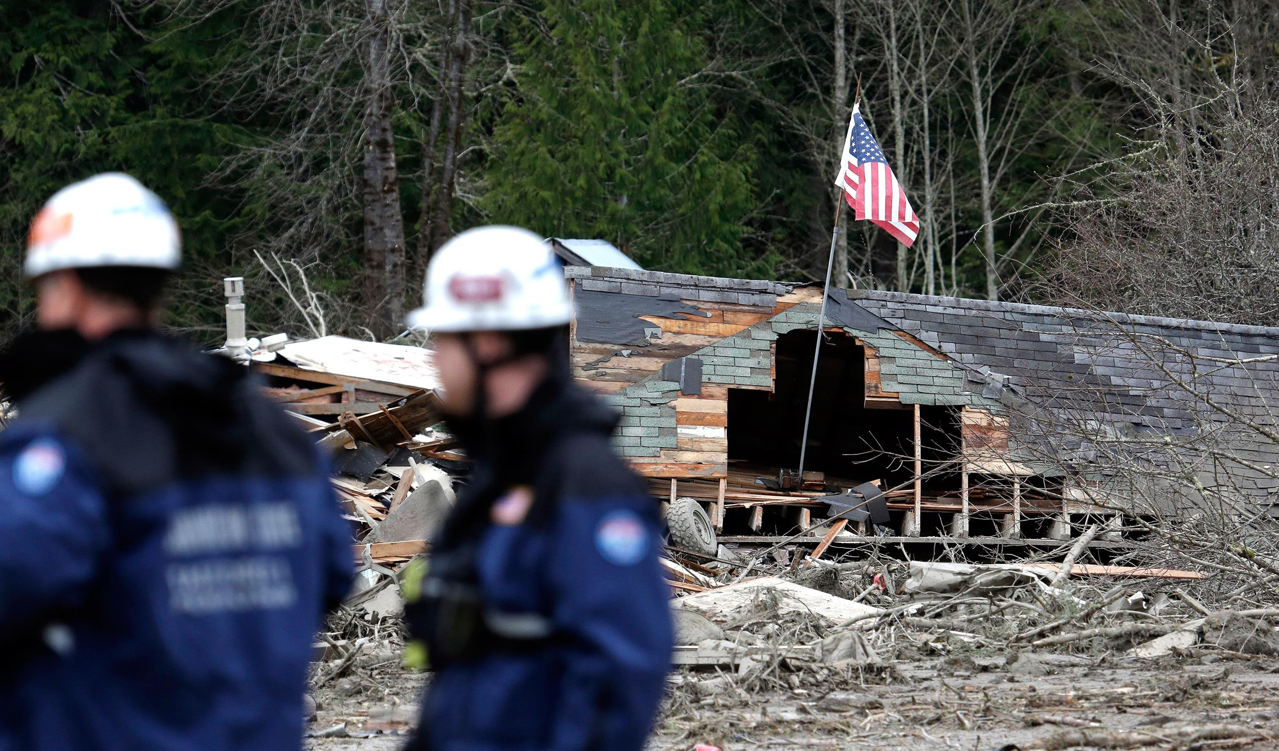 Image: Searchers stand in view of several destroyed homes