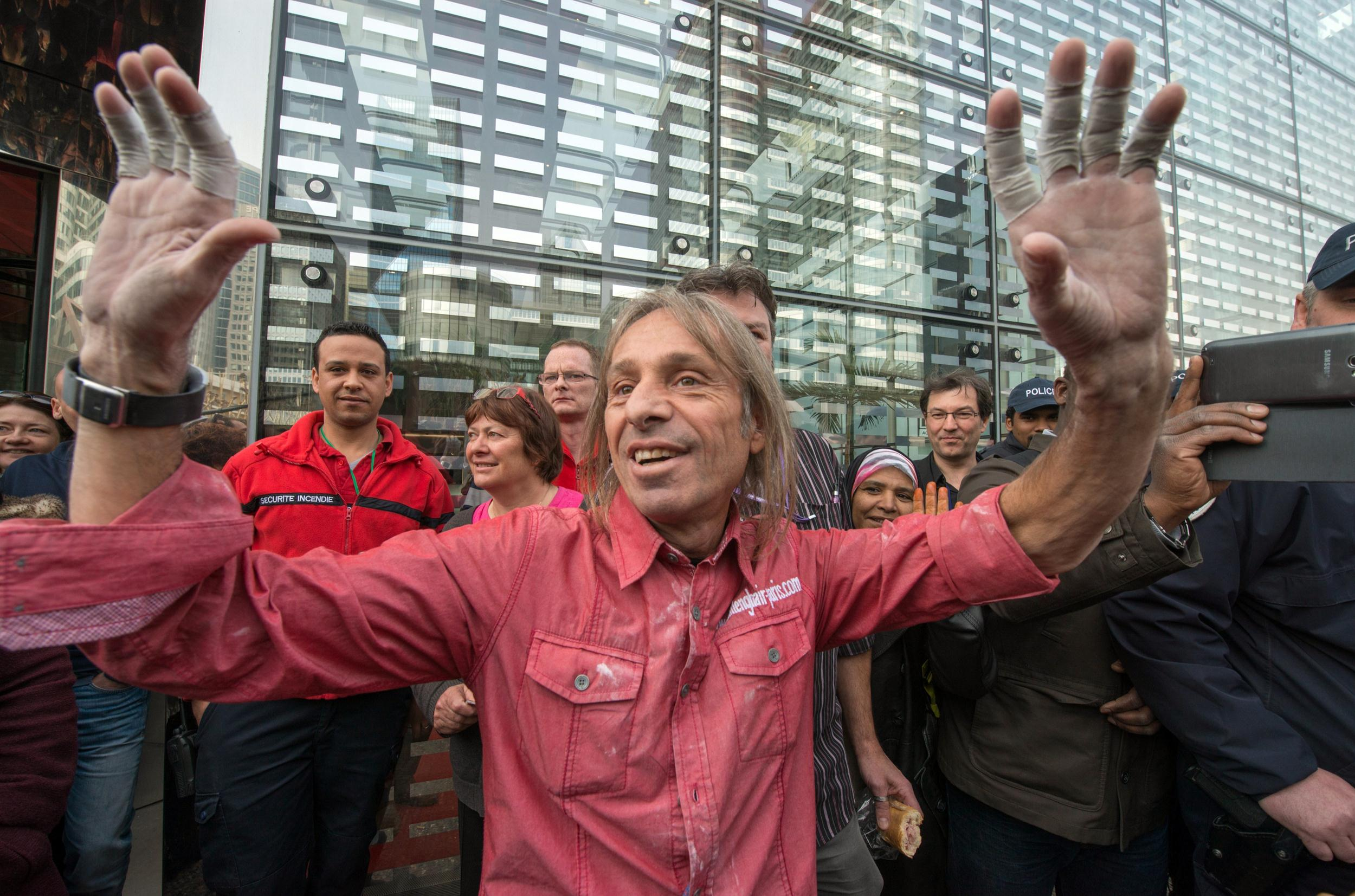 Image: Alain Robert acknowledges the media and onlookers after climbing the Ariane Tower.