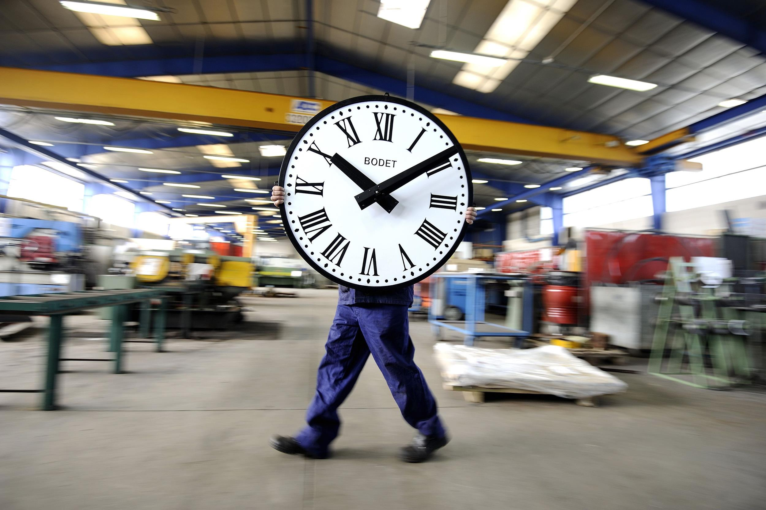 Image: An employee of the Bodet Company carries a clock