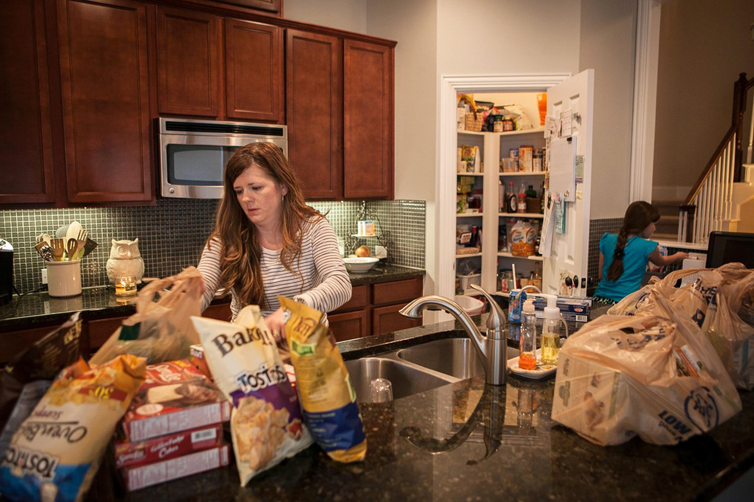 Image: Alice Korey, left, mother of three, unpacks grocery bags from Kroger and uses coupon apps on her iPhone to cut costs of rising food prices at grocery stores