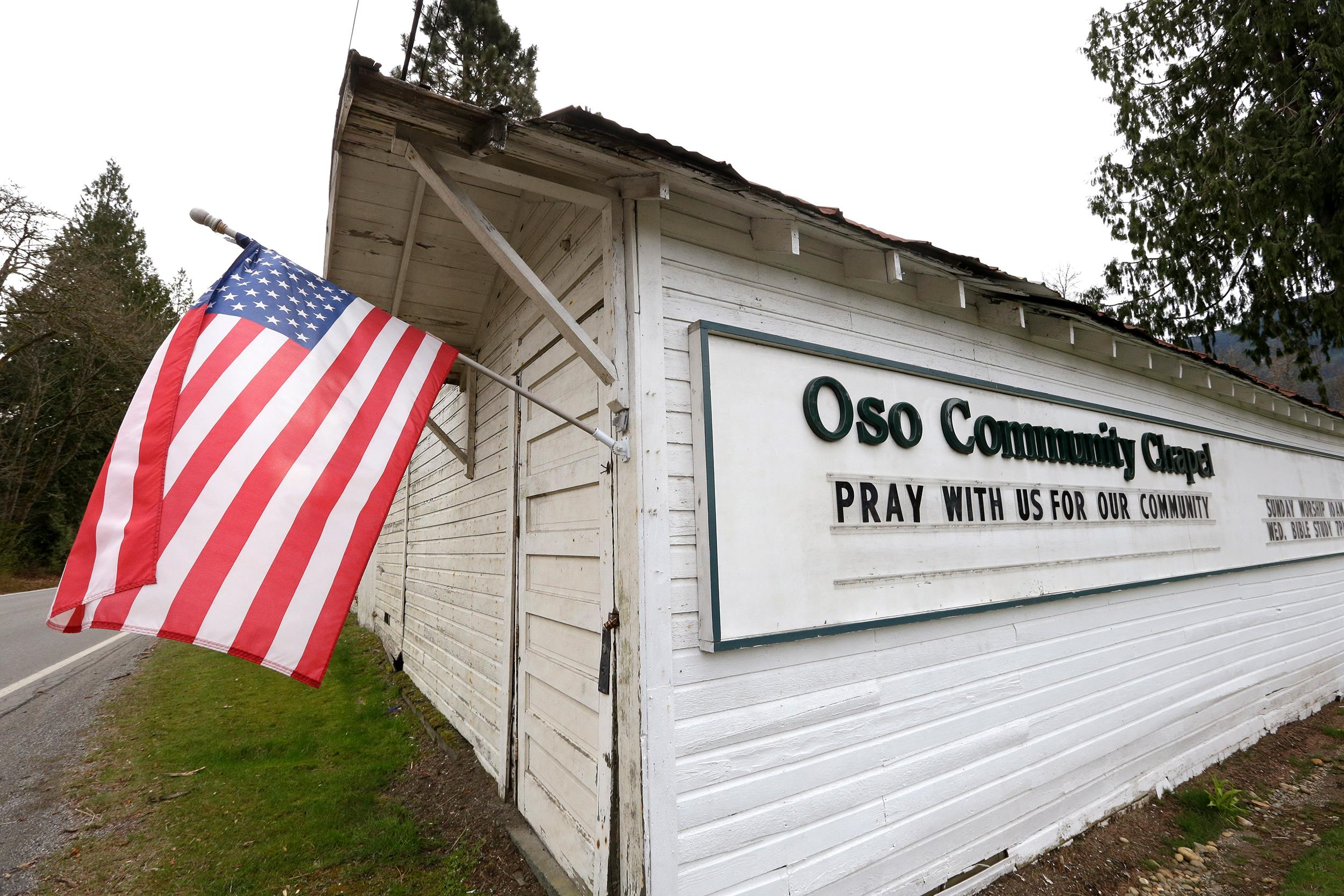 Image: A flag flies from a small church off the highway leading to the scene of a deadly mudslide