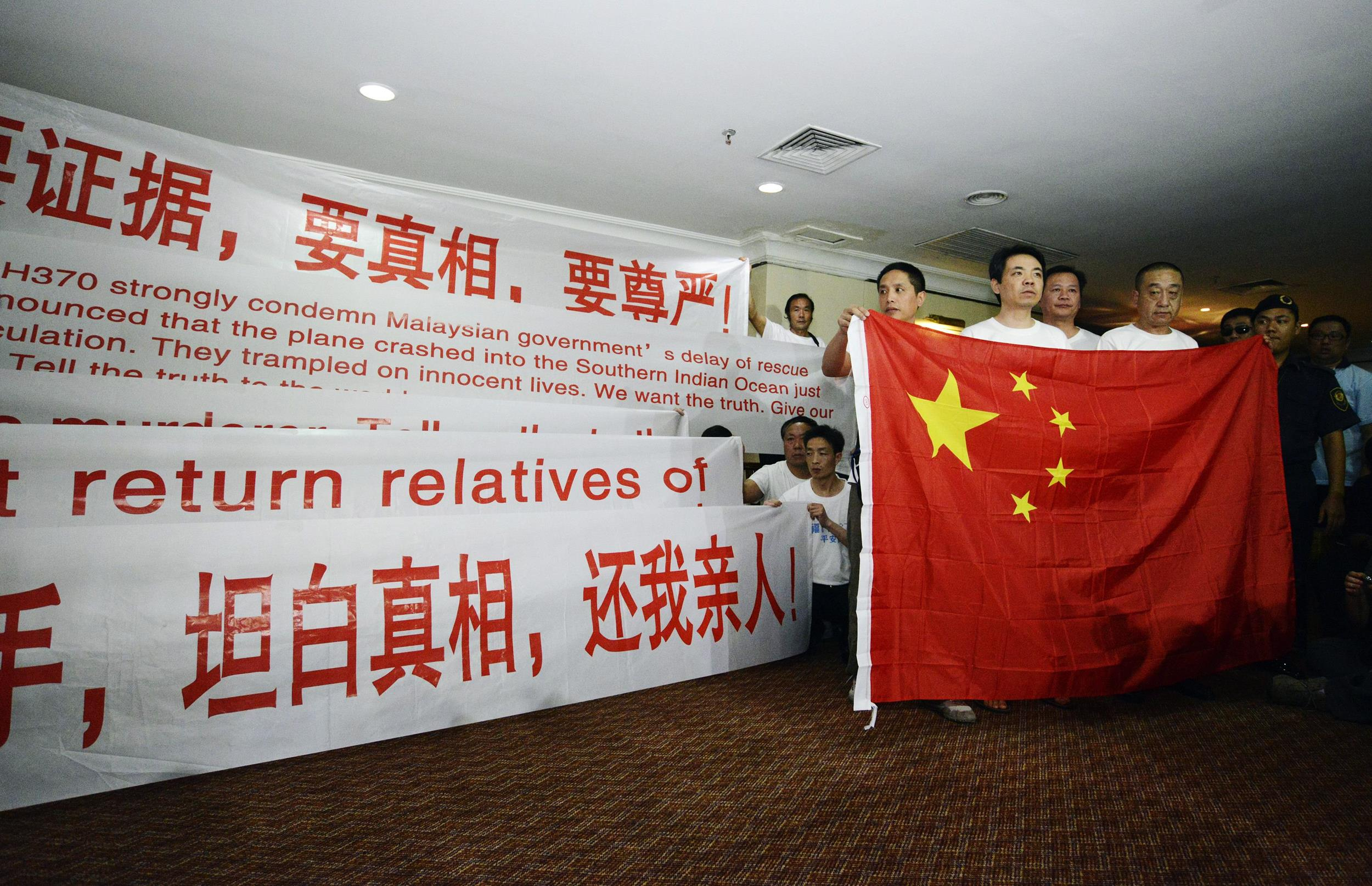 Image: Chinese relatives of passengers from missing Malaysia Airlines flight MH370 display banners and the Chinese flag