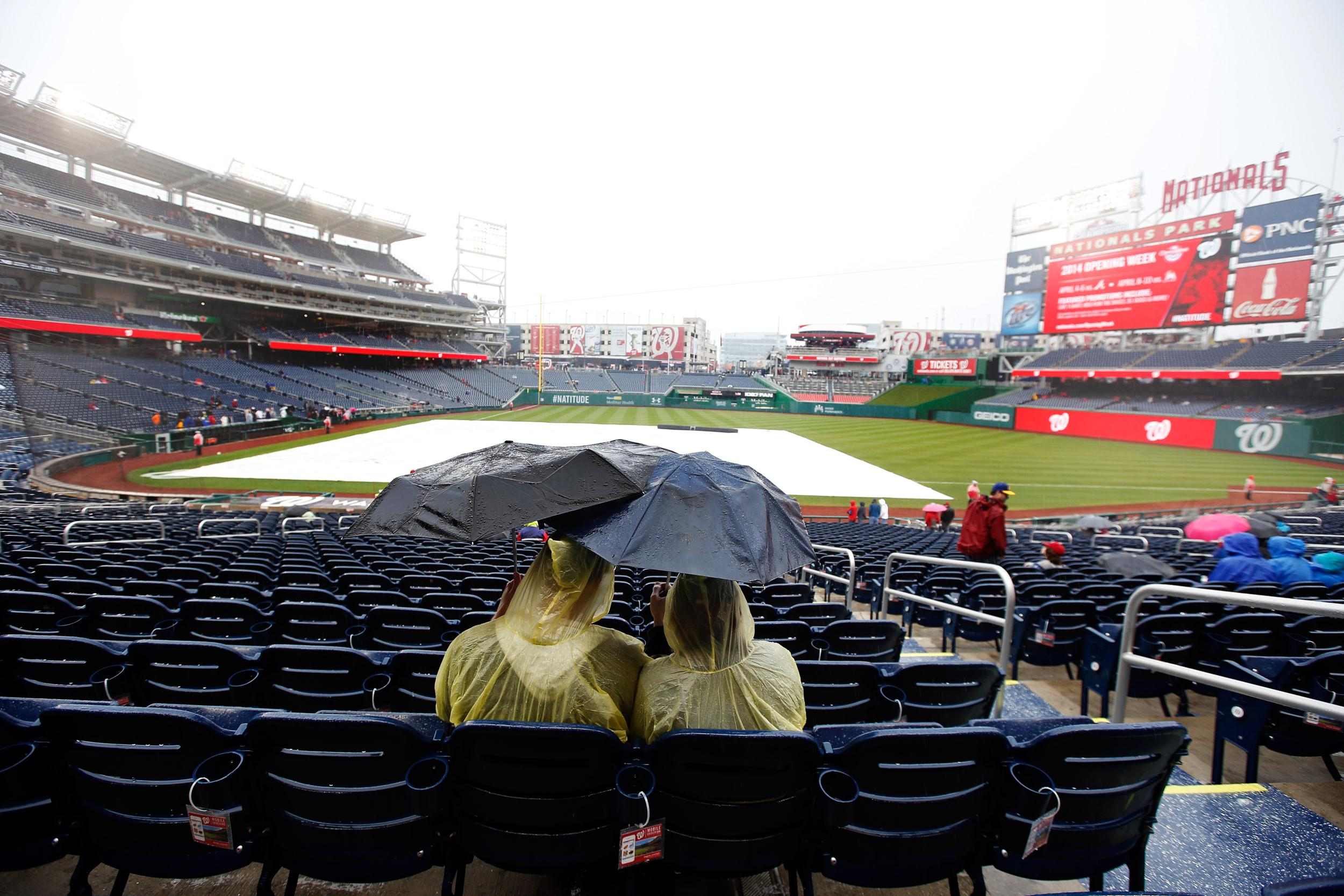 Image: Fans sit under umbrellas in the rain before an exhibition baseball game between the Washington Nationals and the Detroit Tigers at Nationals Park Saturday