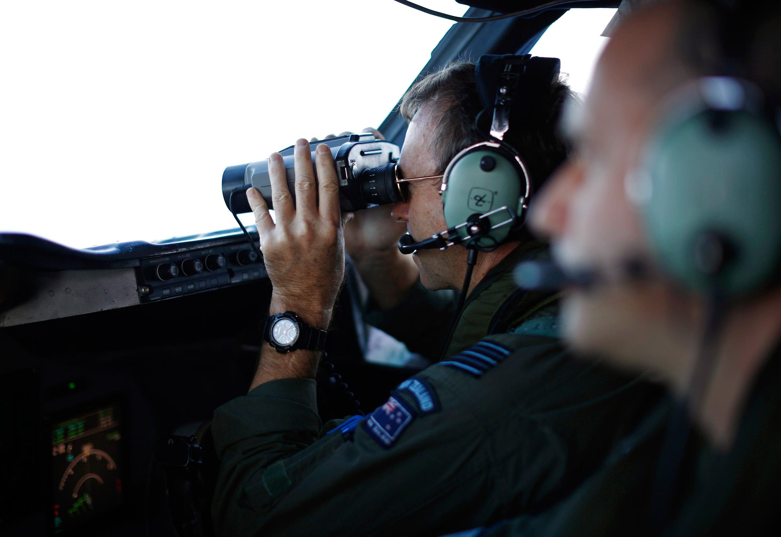 Image: Wing Commander Shearer looks through binoculars on a Royal New Zealand Air Force P-3K2 Orion aircraft during a search for the missing Malaysian Airlines MH370 over the southern Indian Ocean