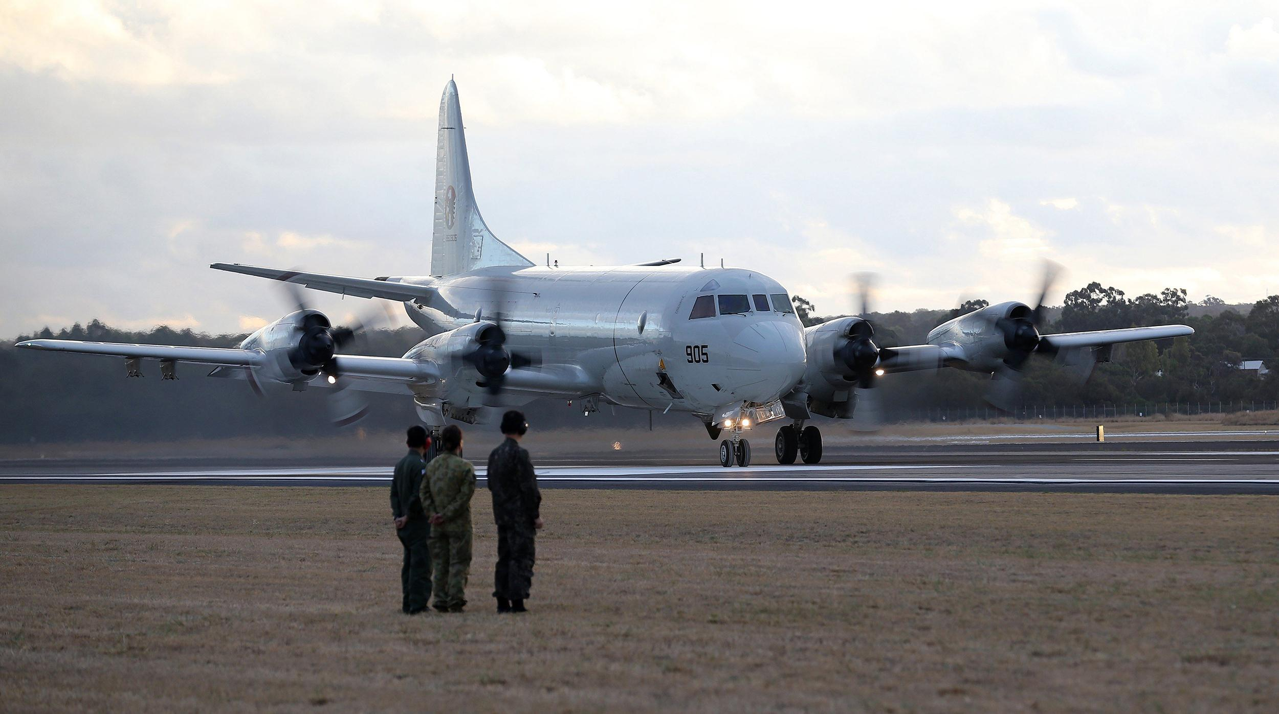 Image: Ground crew look on as a South Korean Navy P-3C Orion taxis after returning from a sortie