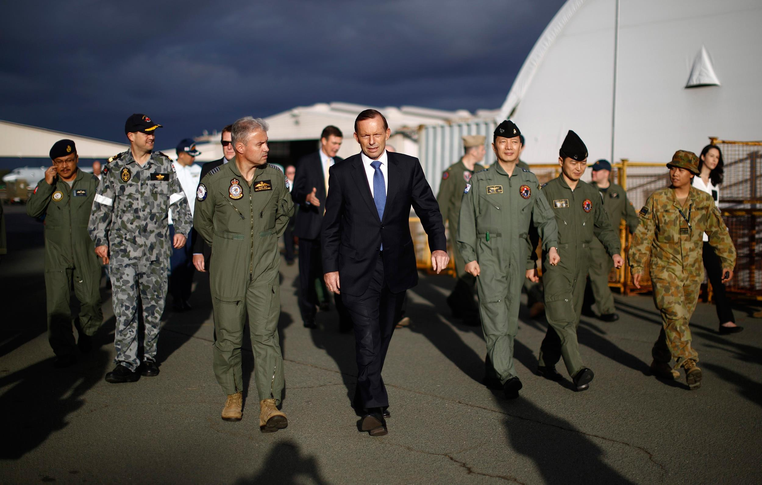 Image: Australia's Prime Minister Tony Abbott walks with Australia's Air Force Group Commander Craig Heap
