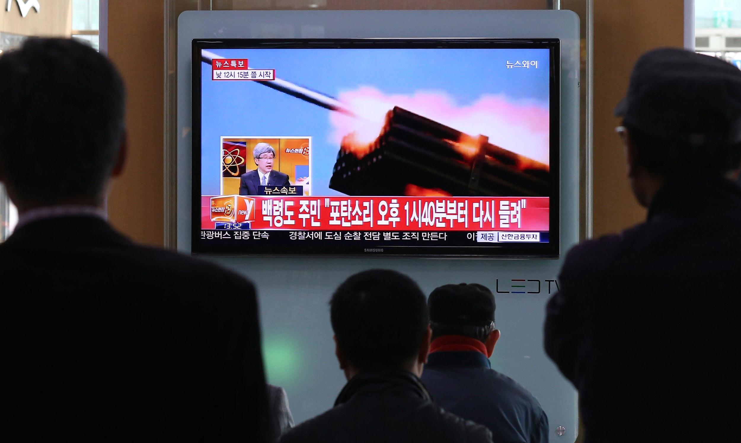 Image: Passengers watch a television program showing reports on North Korea's plan to conduct live-fire drills, at a railway station in Seoul