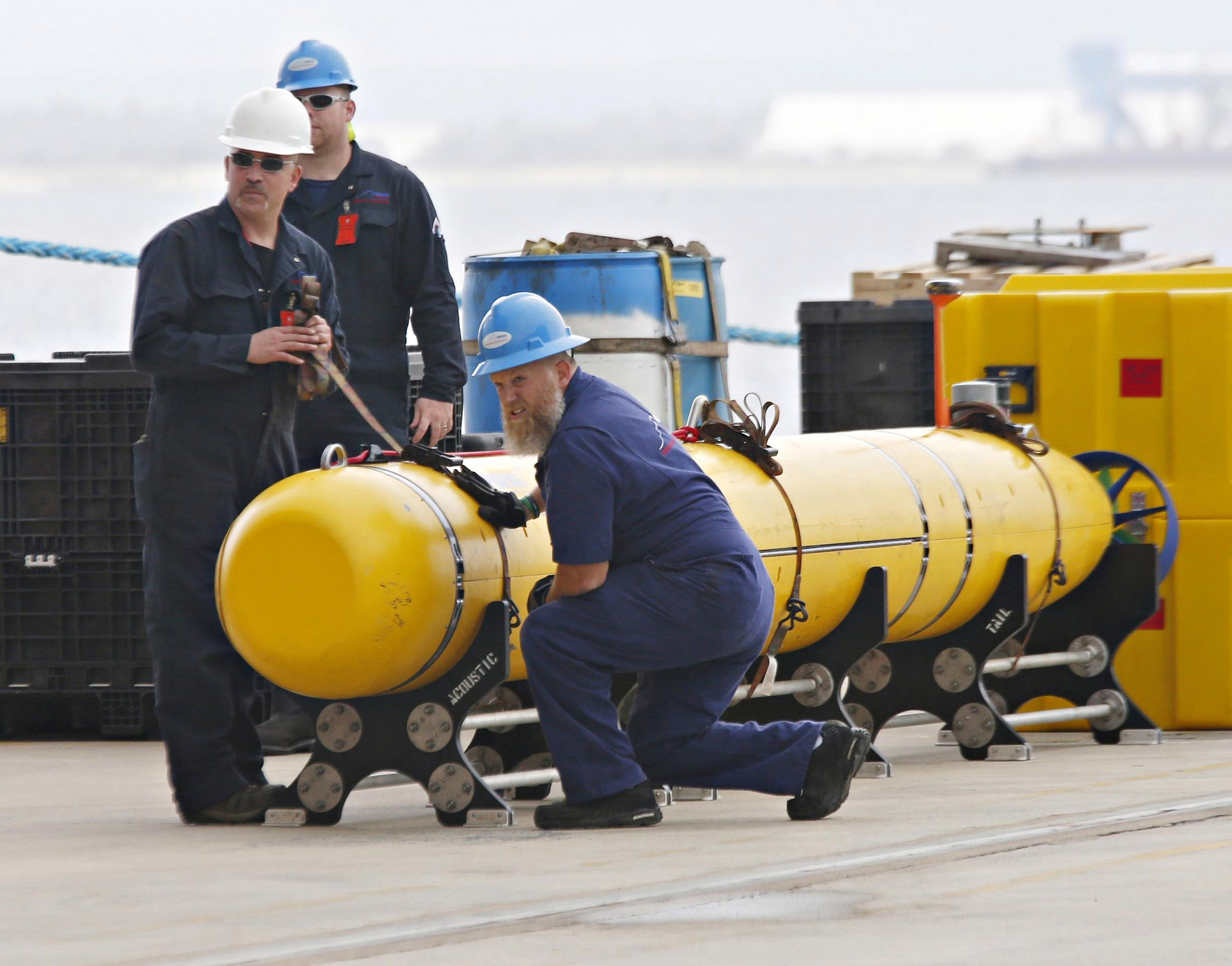 Image: Workers help secure a Phoenix underwater mapping robot before transportation on the dock at HMAS Stirling naval base near Perth