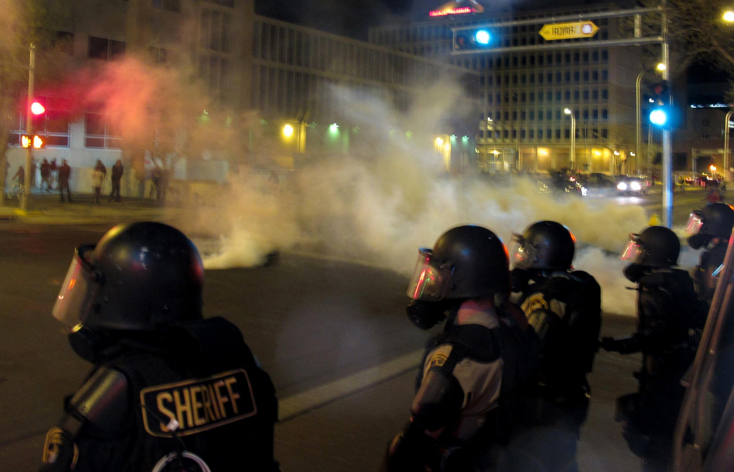 Image: Riot police launch tear gas toward activists in downtown Albuquerque
