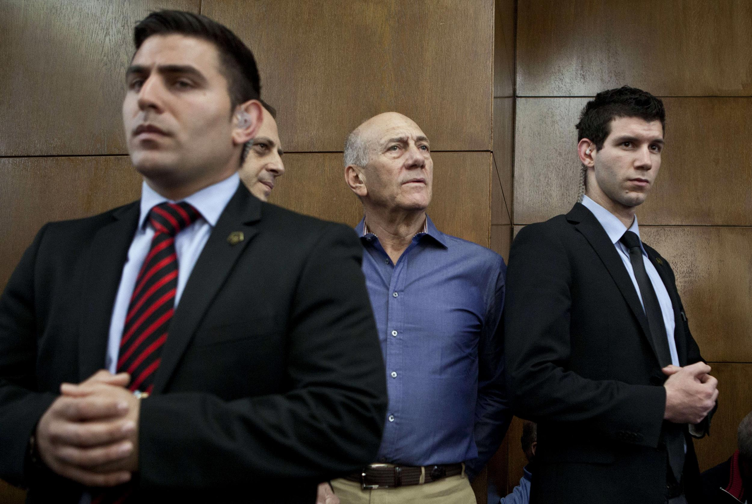 Image: Former Israeli Prime Minister Ehud Olmert, center, waits before the start of a hearing in his trial for corruption