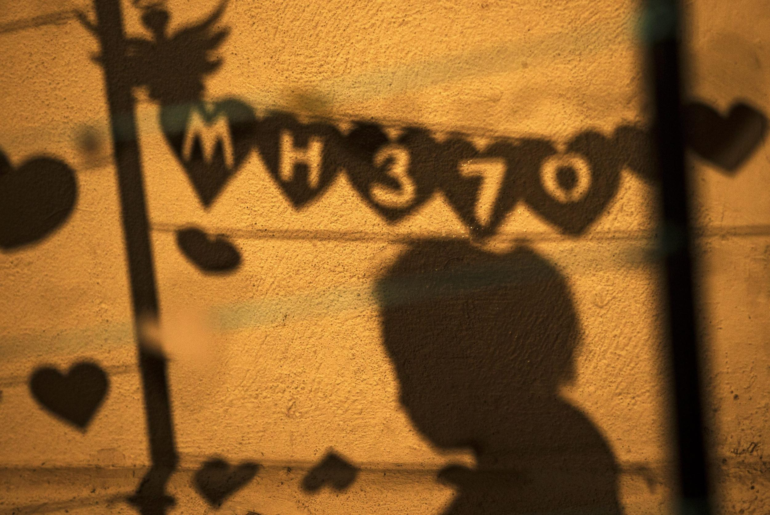 Image: Shadows of people hanging messages during an event 'Love U MH370' in Kuala Lumpur