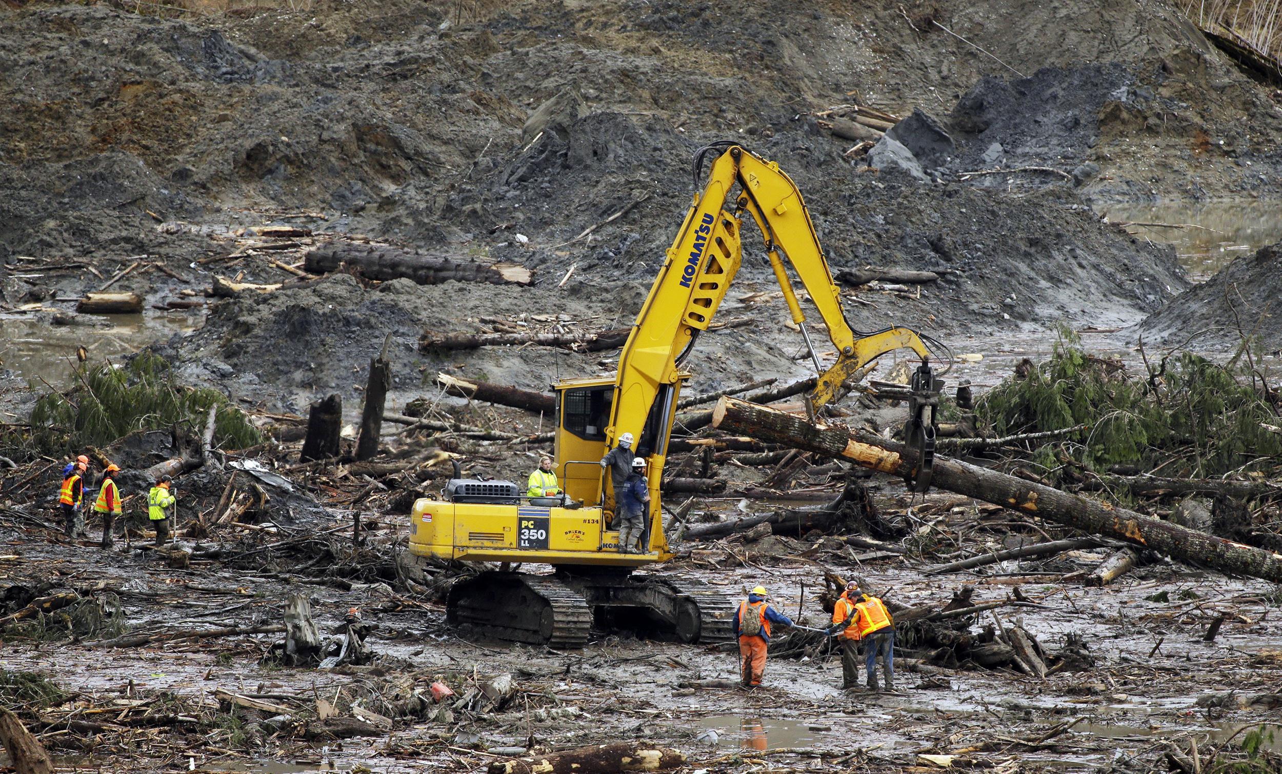 Image: Workers move a log Sunday, near Darrington, Wash.