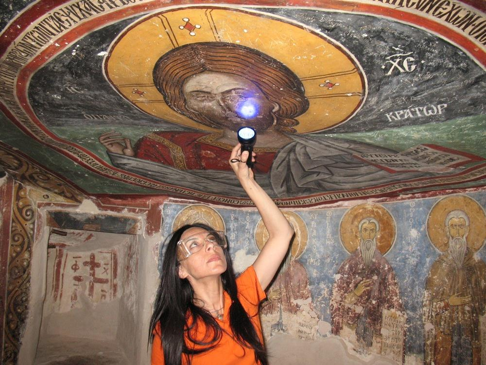 Image: UCLA archaeologist Ioanna Kakoulli examines a painting in the monastery under UV light