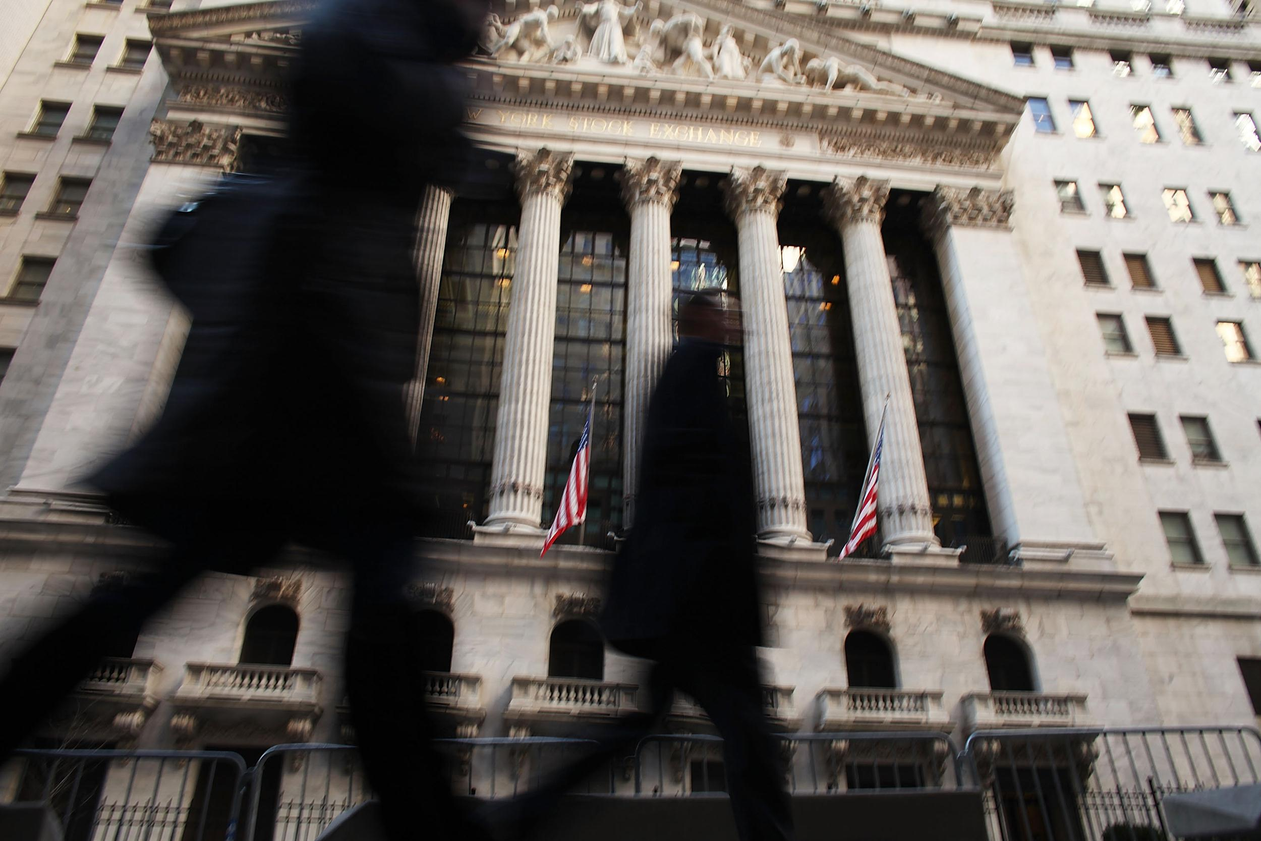 Image: People walk by the front of the New York Stock Exchange