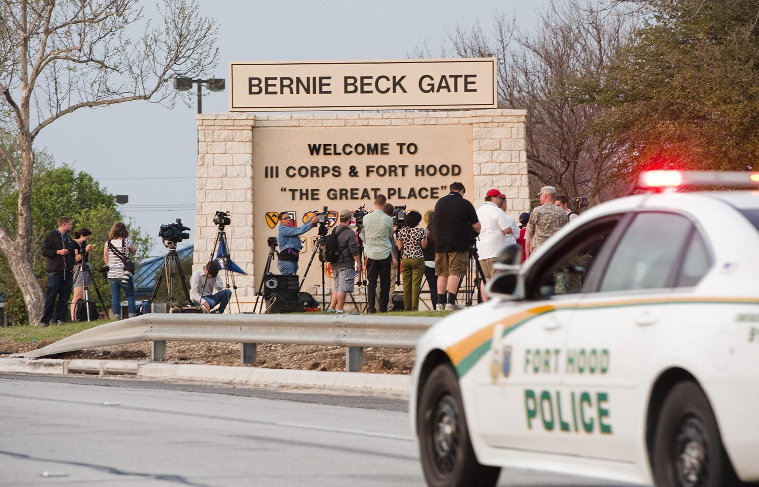 Image: News media gather outside one of the entrances to Fort Hood military base near Killeen, Texas,