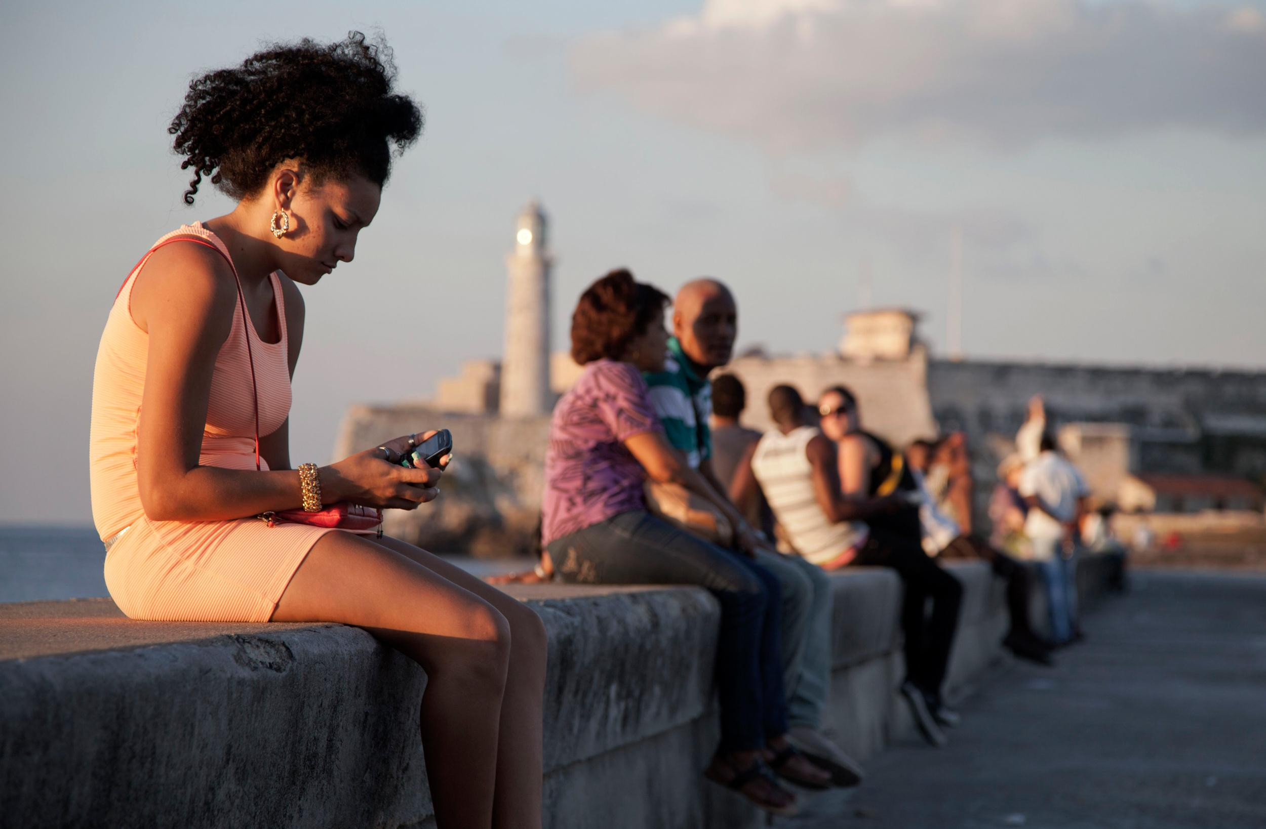 Image: A woman uses her cellphone as she sits on the Malecon in Havana, Cuba