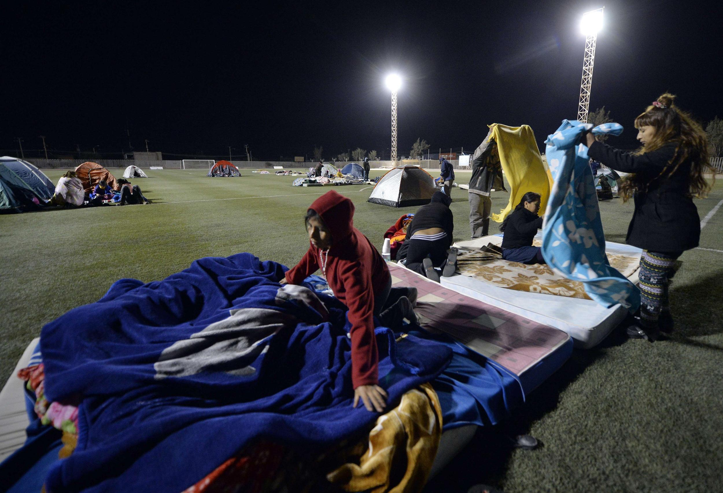Image: People from the town of Pozo al Monte, close to the city of Iquique, camp out on a stadium field