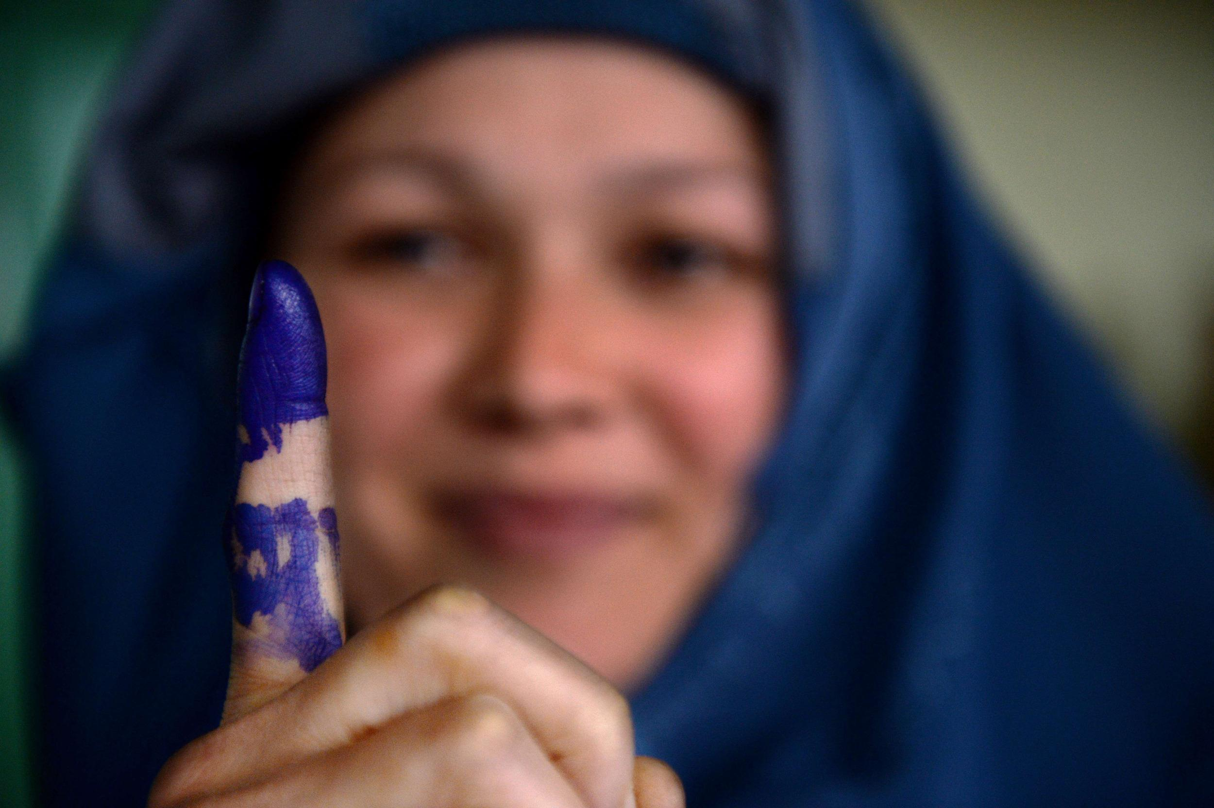 Image: Afghan voter shows her inked finger after she cast her ballot in Kabul