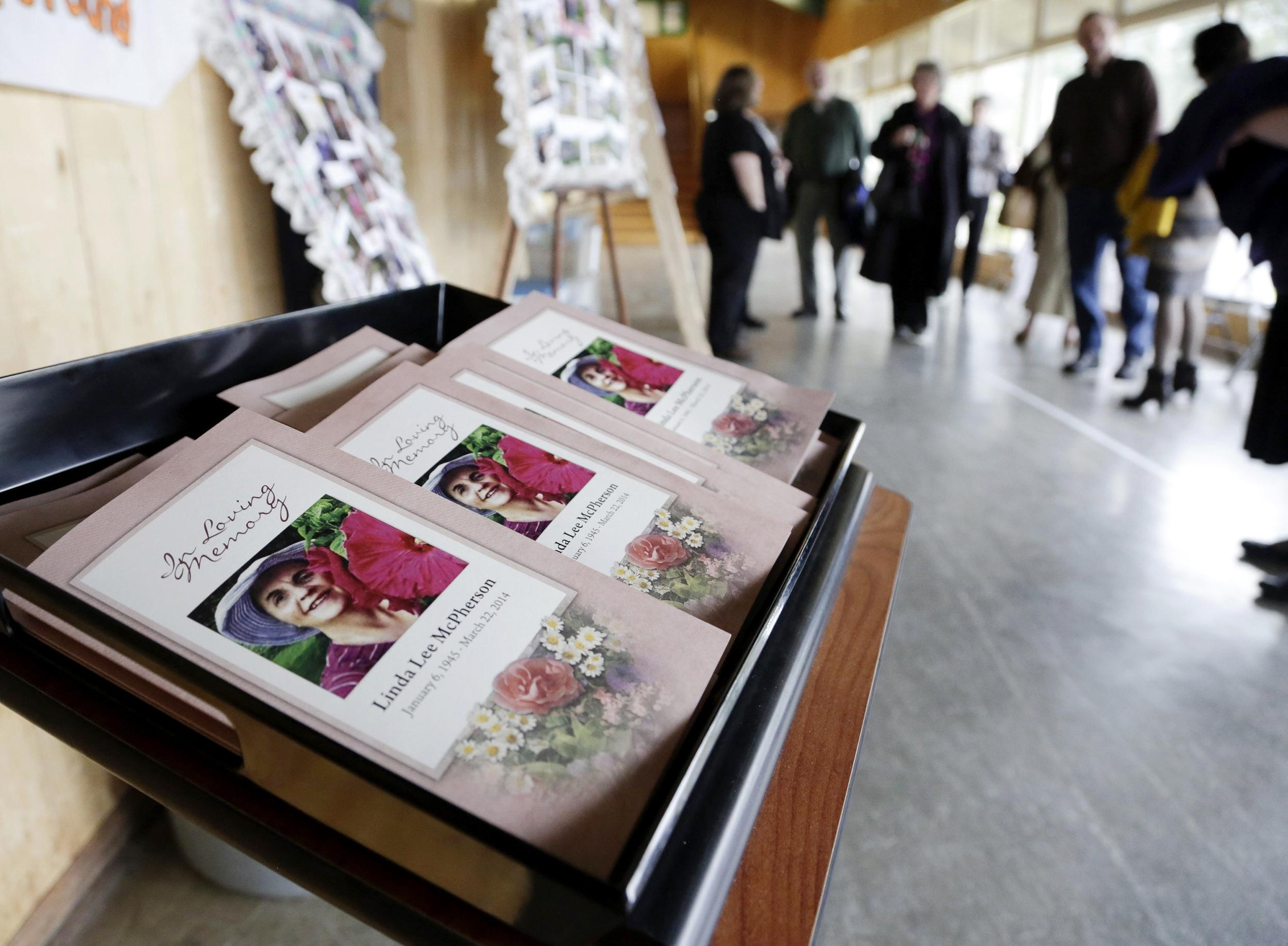 Image: Funeral programs are seen as people arrive for funeral services for McPherson at the Community Center in Darrington