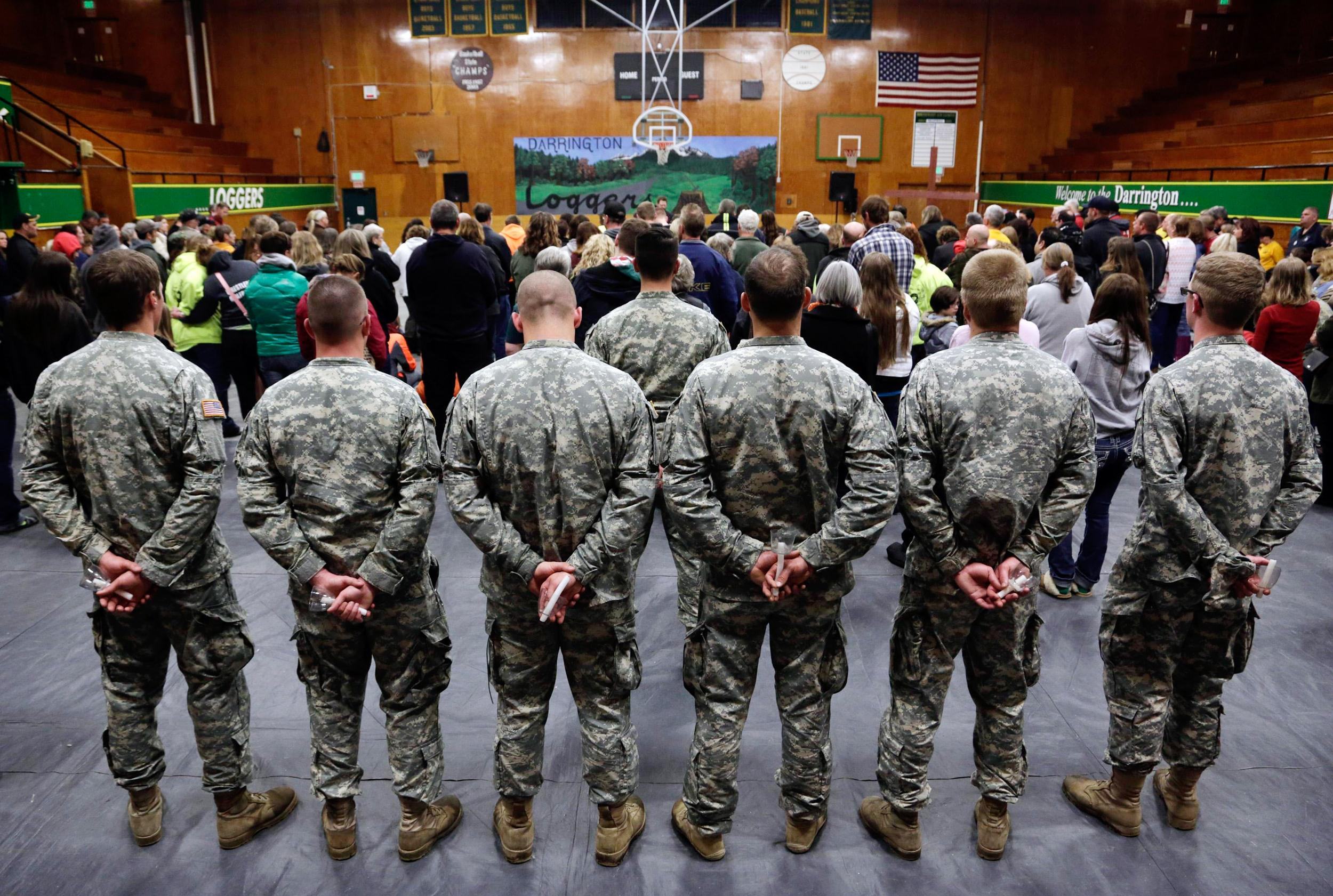 Image: Washington Army National Guard Members of 790th Chemical Company attend a candlelight vigil for communities affected by the Oso mudslide at the Community Center in Darrington, Washington