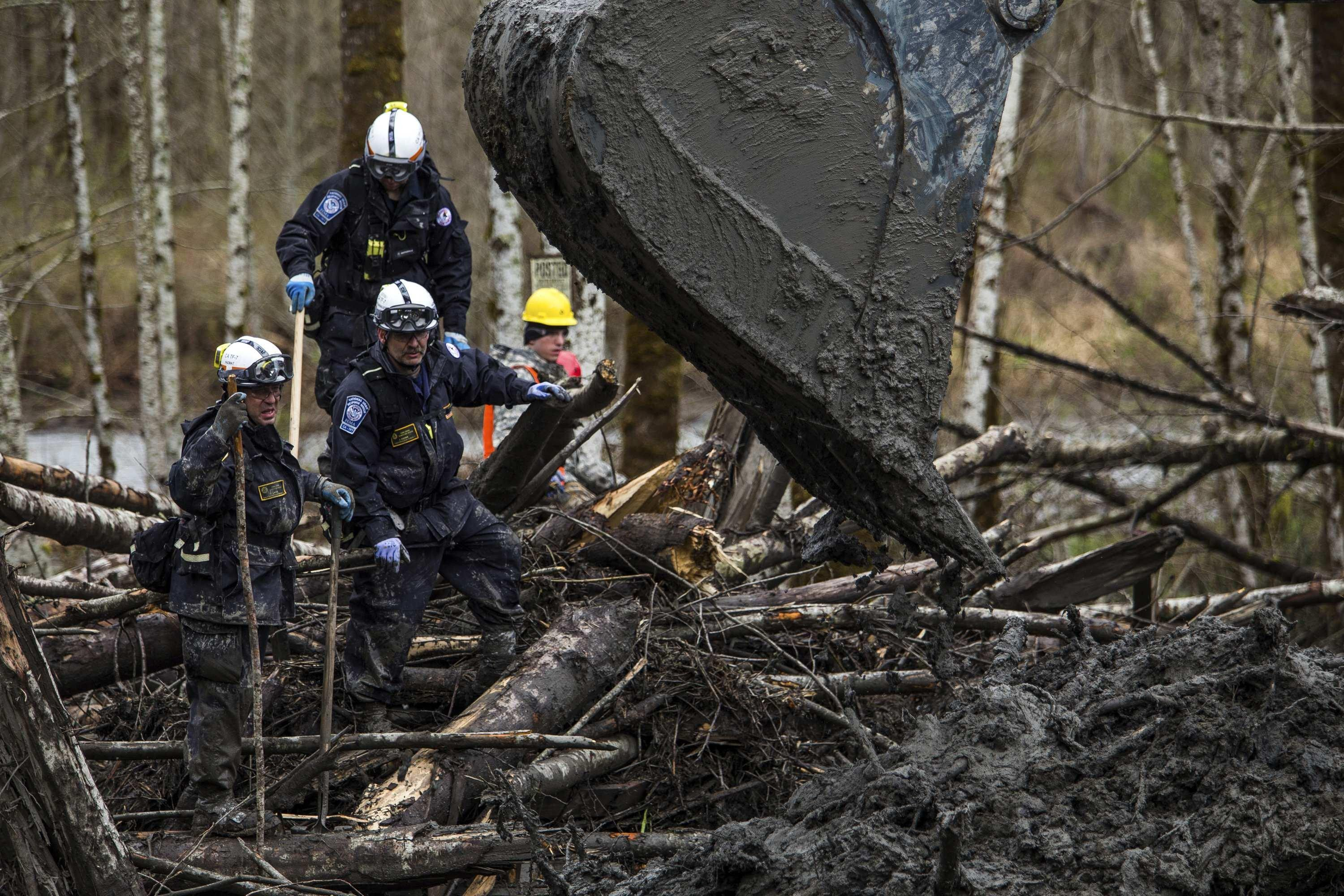 Image: Rescuers watch carefully as an excavator combs through the large debris pile left by a mudslide in Oso.
