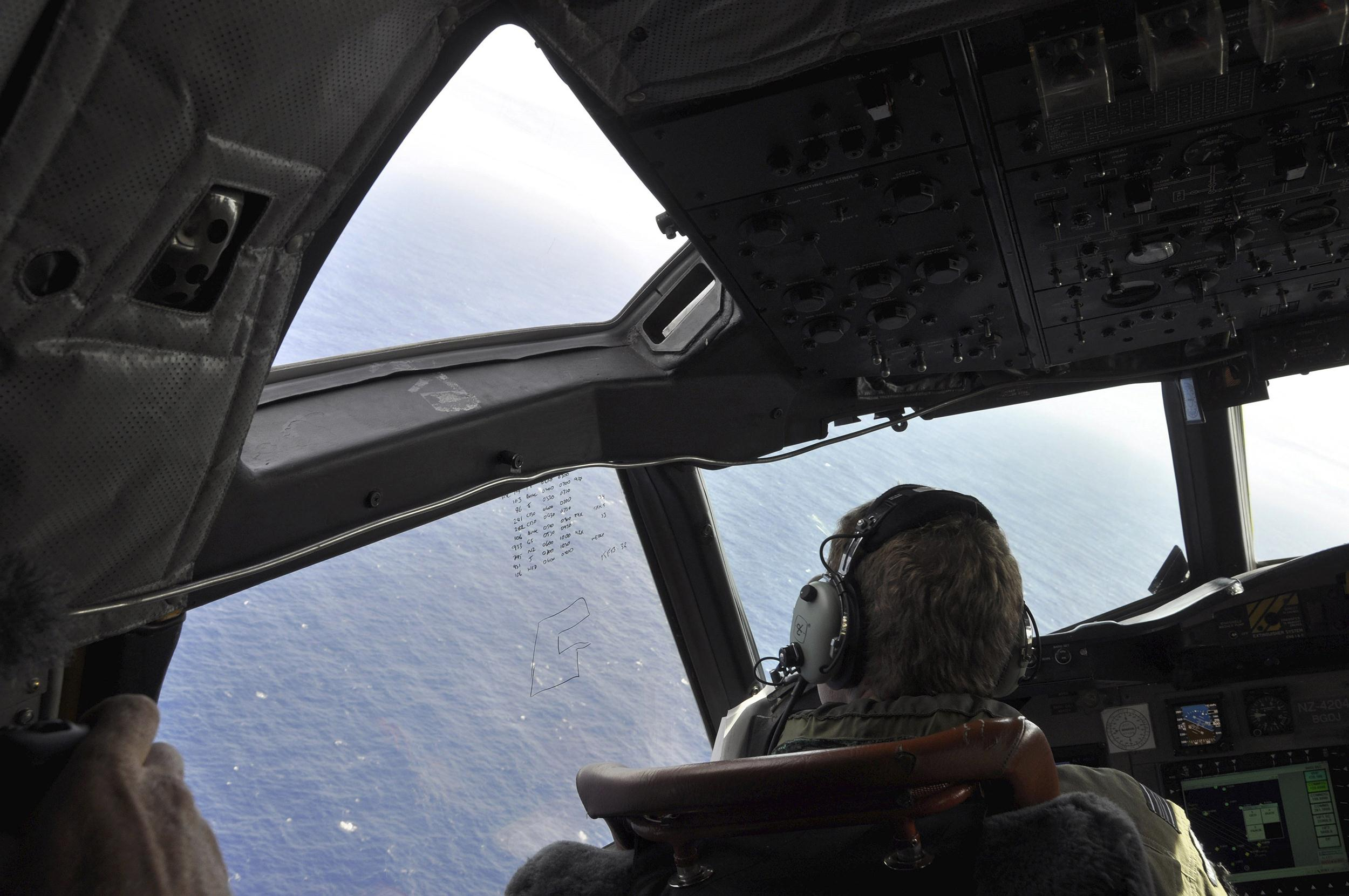 Image: A crewman on a search plane looks for debris from the missing Malaysia Airlines Flight MH370, on April 1.