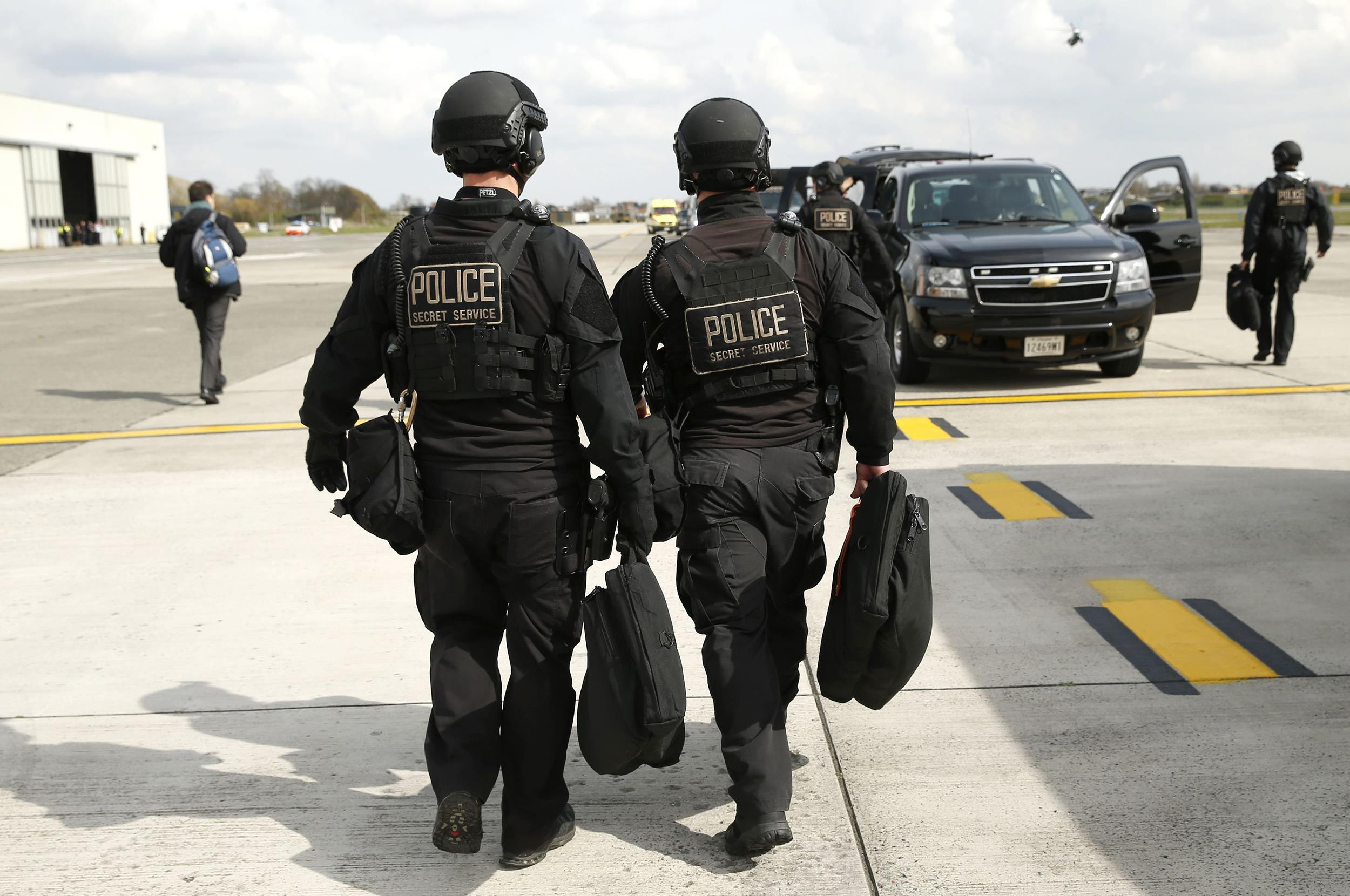 Image: Two Secret Service CAT team members walk toward their motorcade vehicle at Brussels Airport