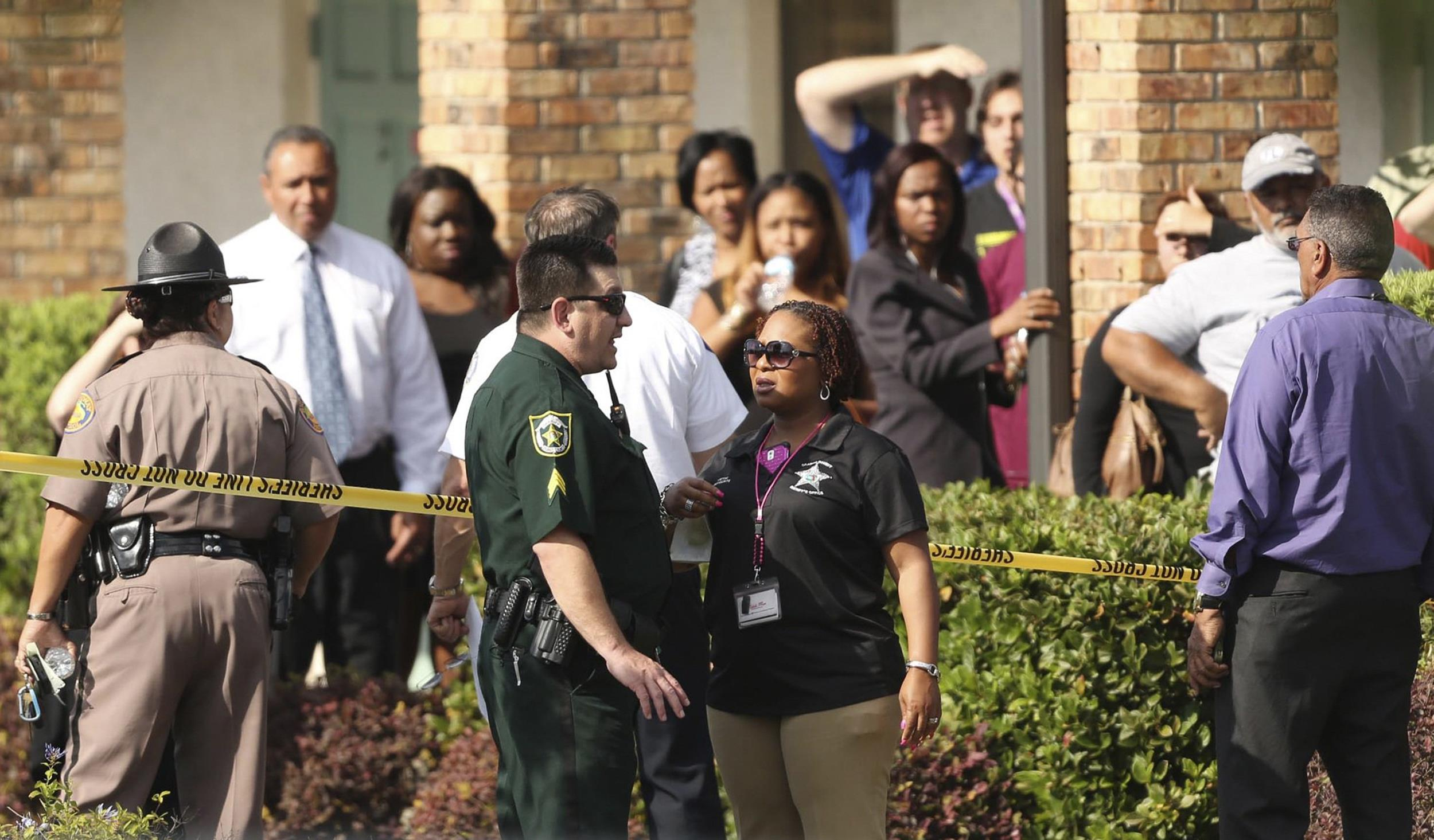 Image: Parents wait behind as police consult after several children were injured after being struck by a vehicle at a KinderCare Learning Center in Winter Park