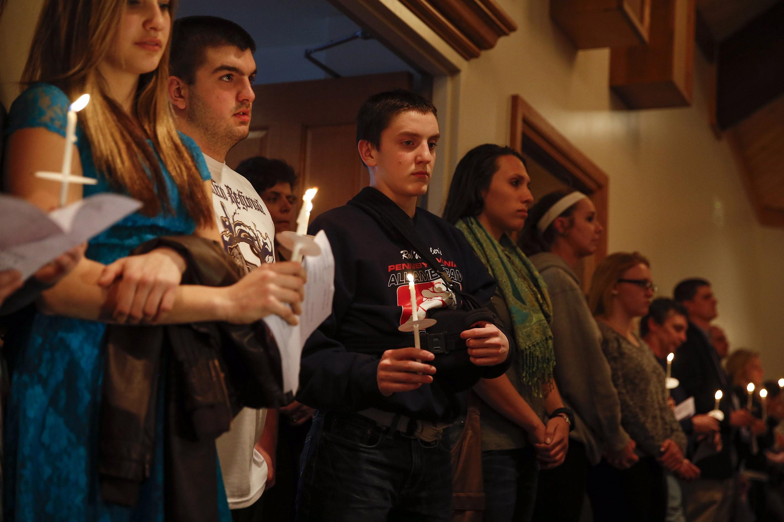 Image: People hold candles during a prayer vigil for victims of the Franklin Regional High School stabbing rampage, at a church in Murrysville