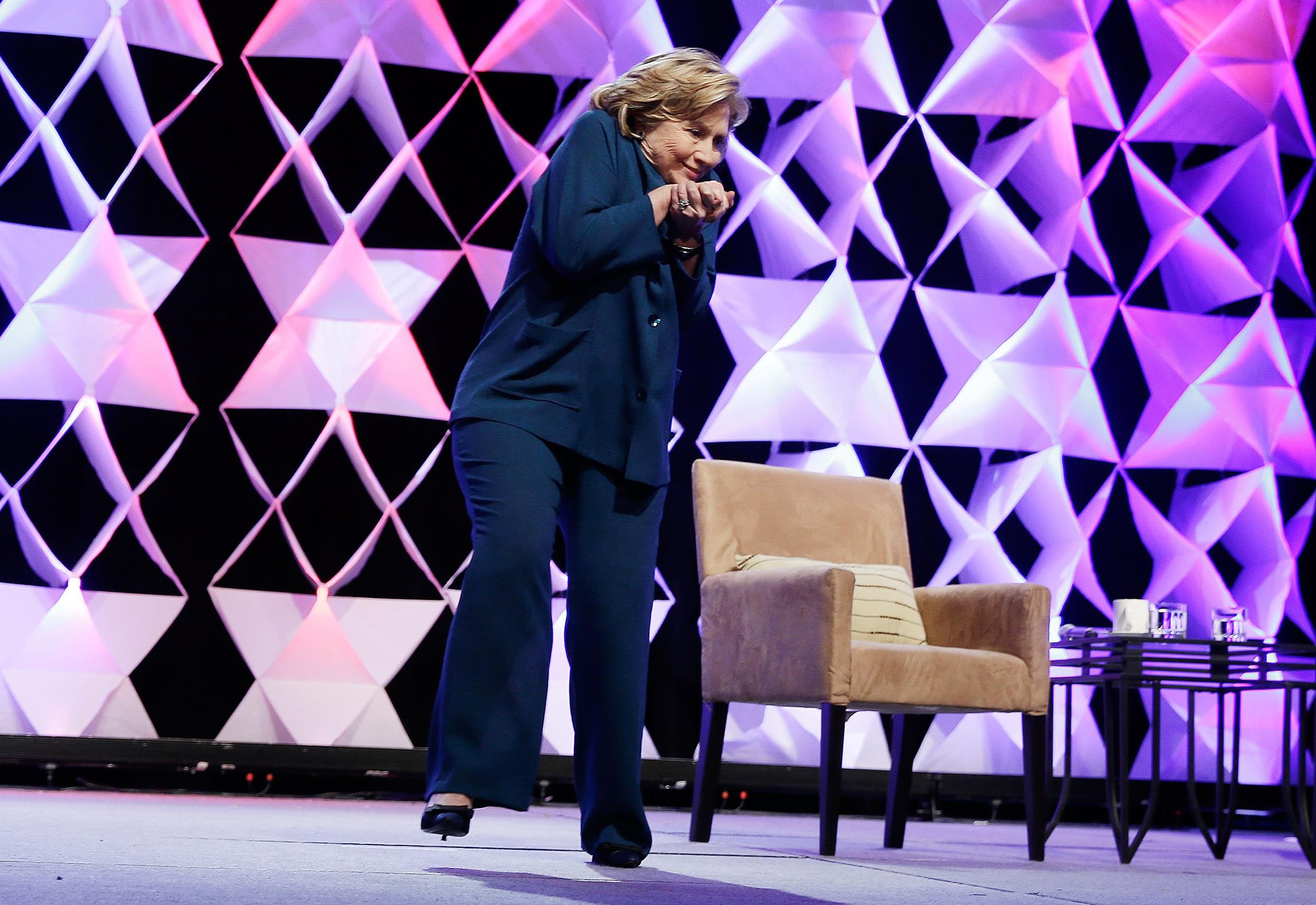 Image:  Former Secretary of State Hillary Clinton ducks after a woman threw an object toward her