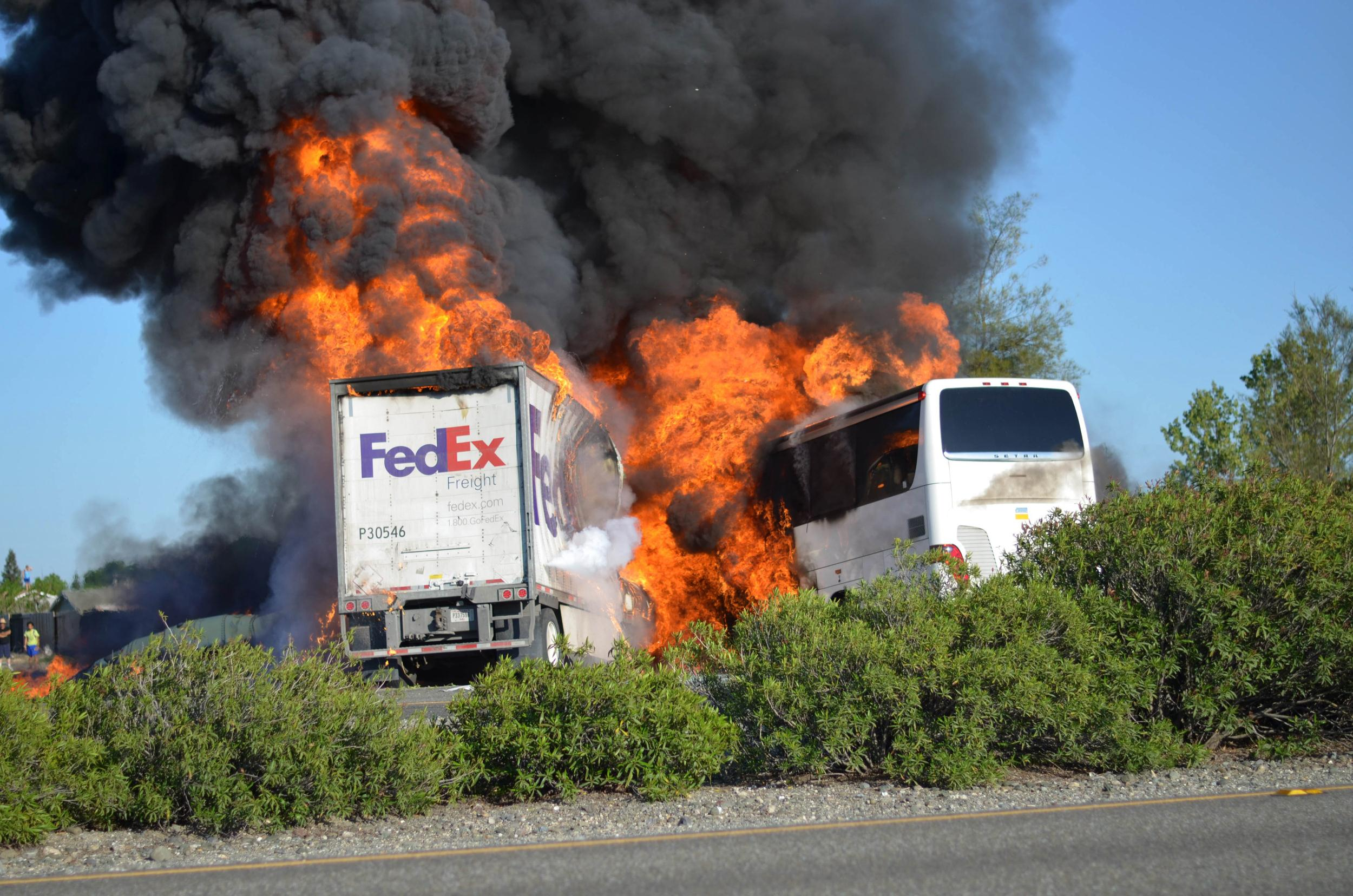 Image: Massive flames are seen devouring both vehicles just after a crash involving a FedEx tractor-trailer and a bus
