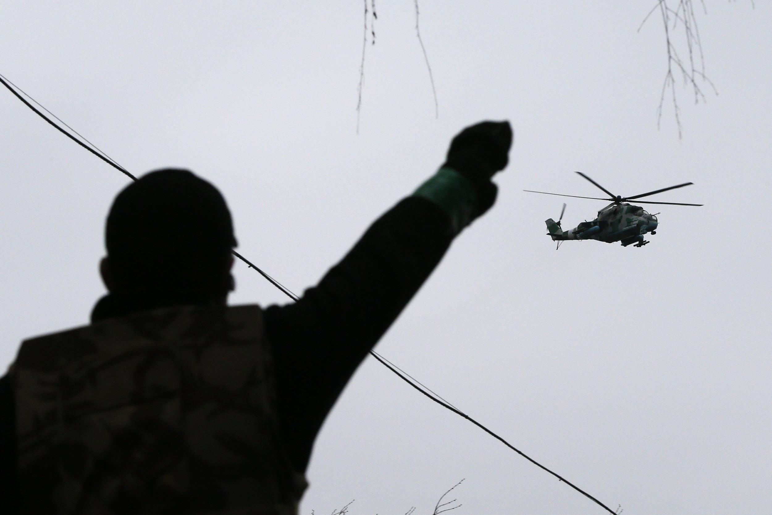Image: A man gestures while pro-Russian protesters gather at the police headquarters, while a military helicopter flies above, in Slaviansk