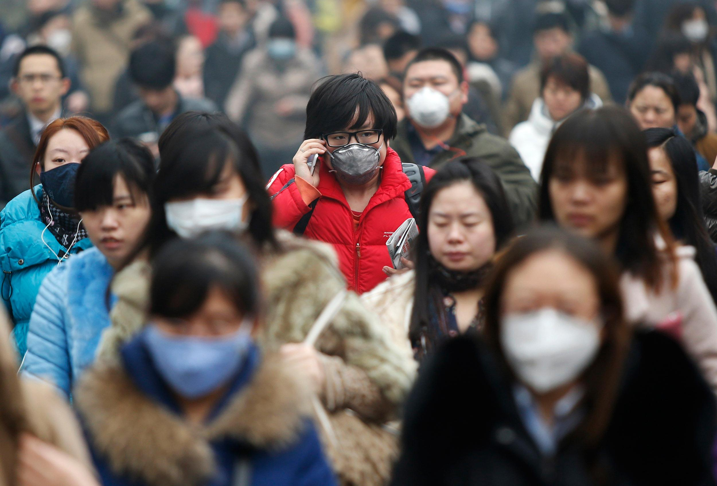 Image: File photo of commuters wearing masks making their way amid thick haze in the morning in Beijing